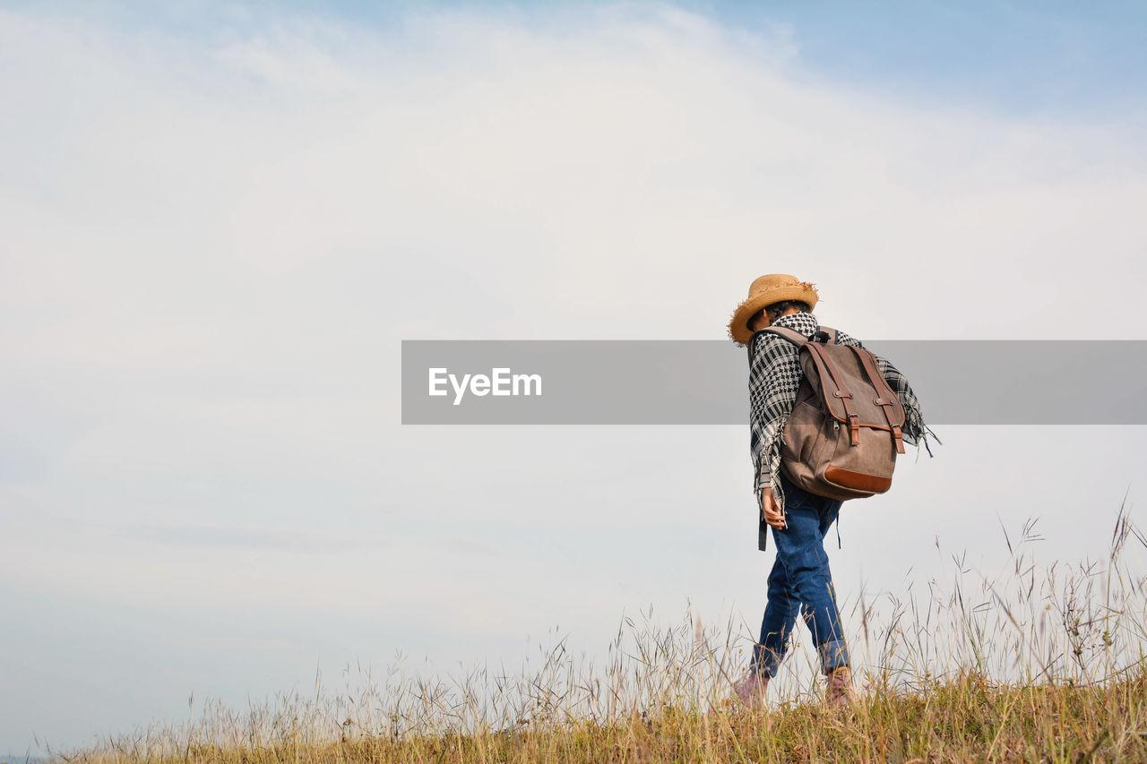 Girl Walking On Grassy Field Against Sky