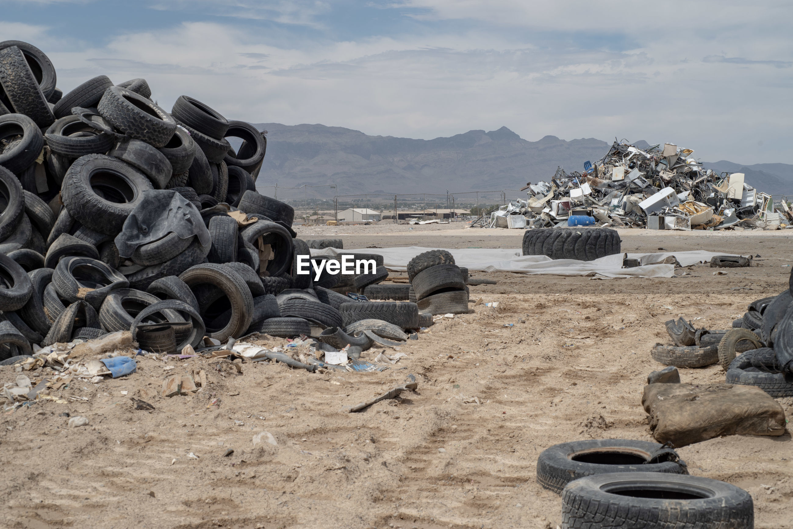 Piles of worn out tires in mojave desert landscape with mountain range in background
