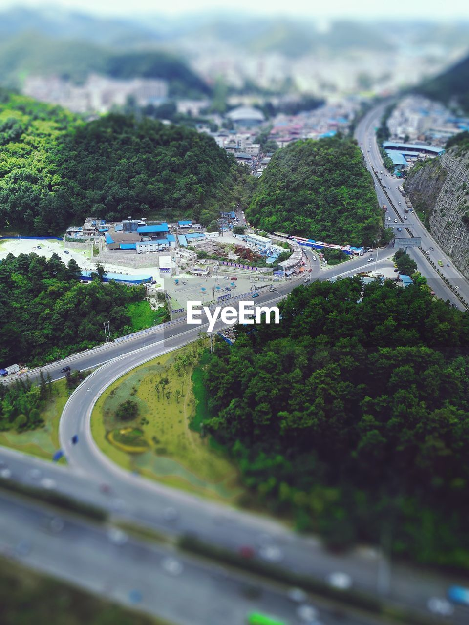 road, transportation, day, high angle view, tree, car, mode of transport, no people, outdoors, nature, built structure, architecture, sky, tilt-shift