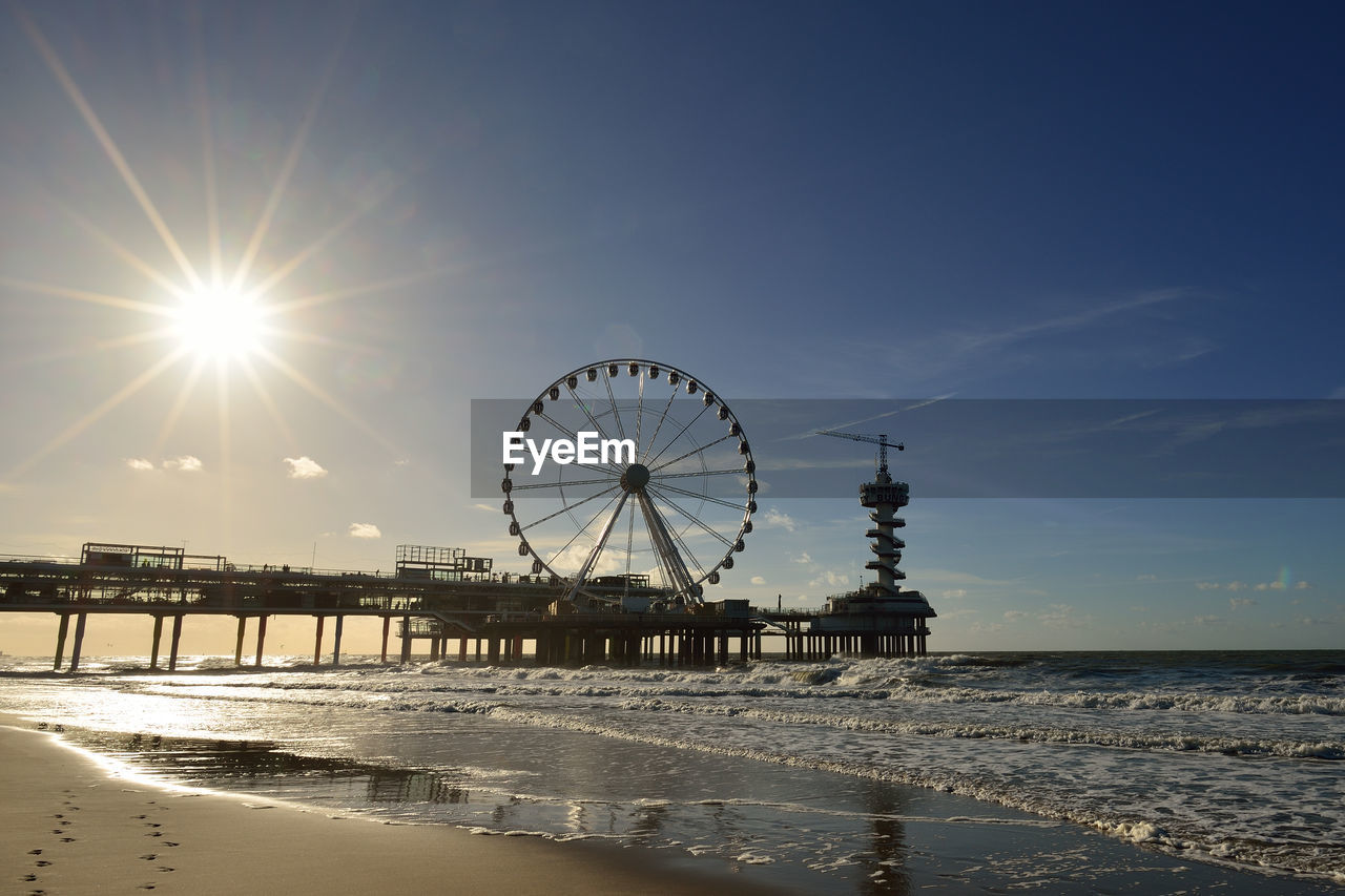 Ferris wheel and pier by sea against sky