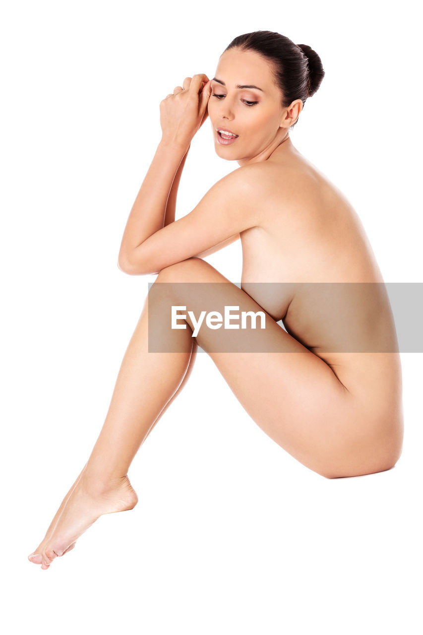 Naked Young Woman Crouching Against White Background