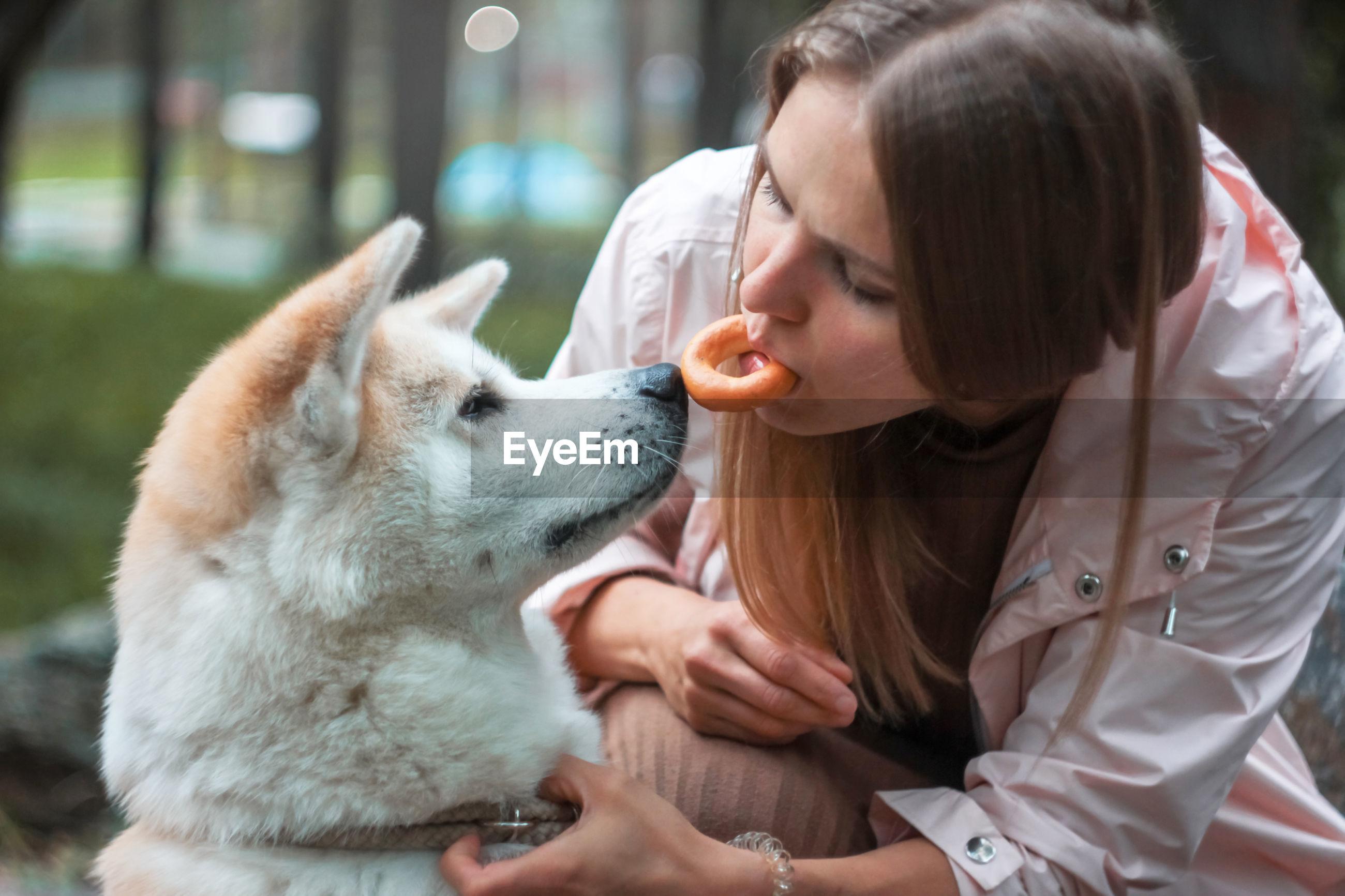 Woman feeding dog outdoors