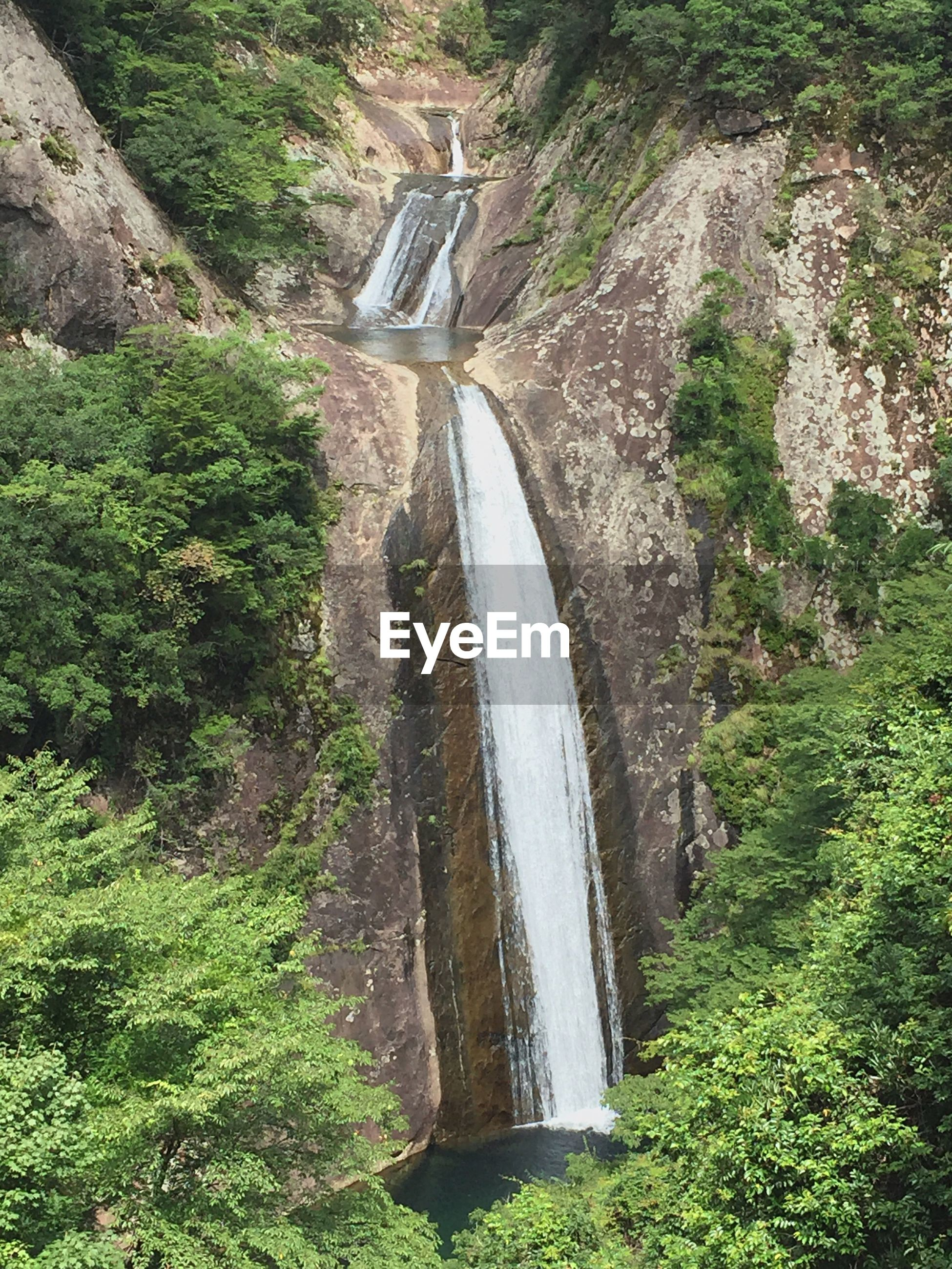 SCENIC VIEW OF WATERFALL BY MOUNTAIN
