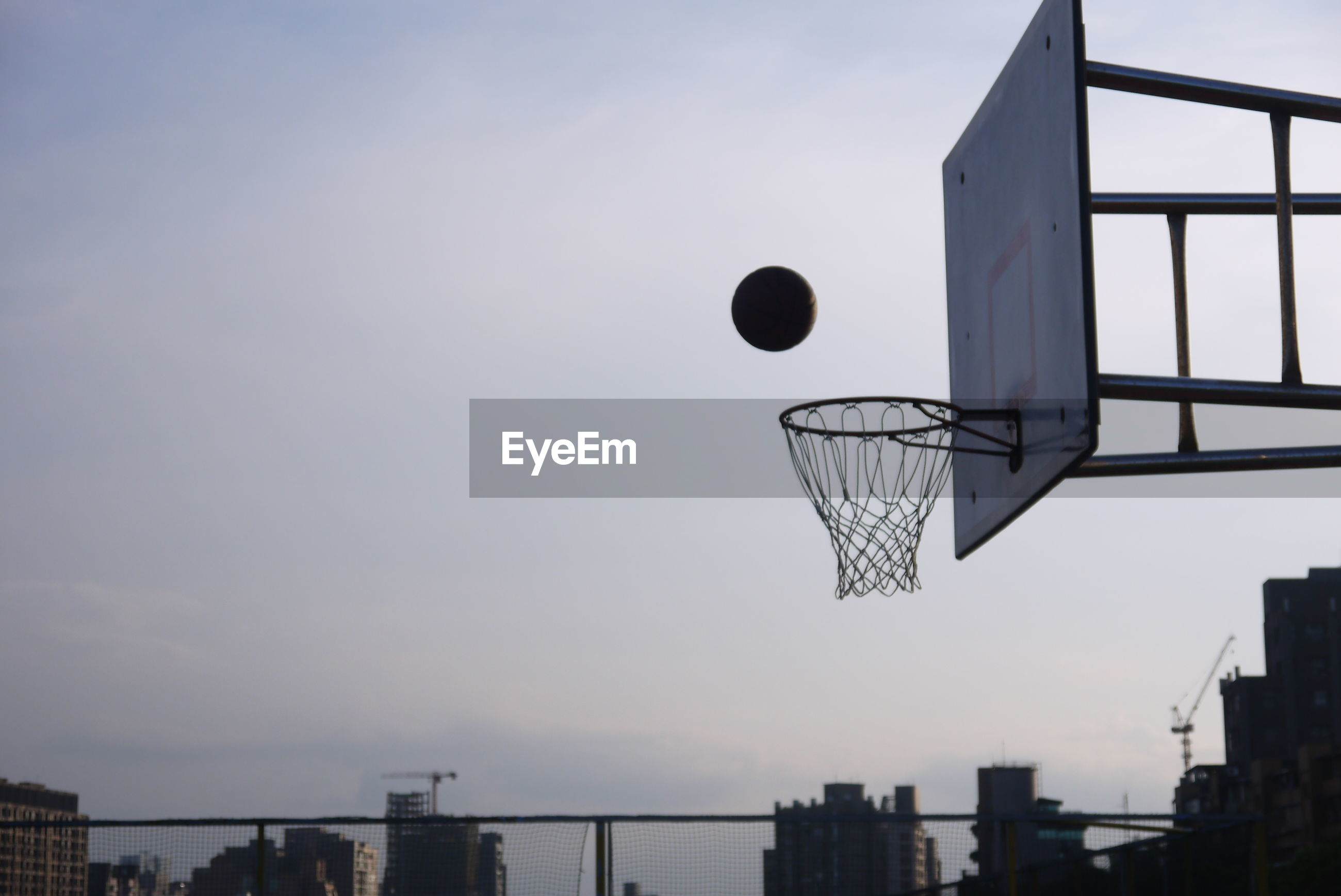 Low angle view of basketball going in hoop against sky during sunset
