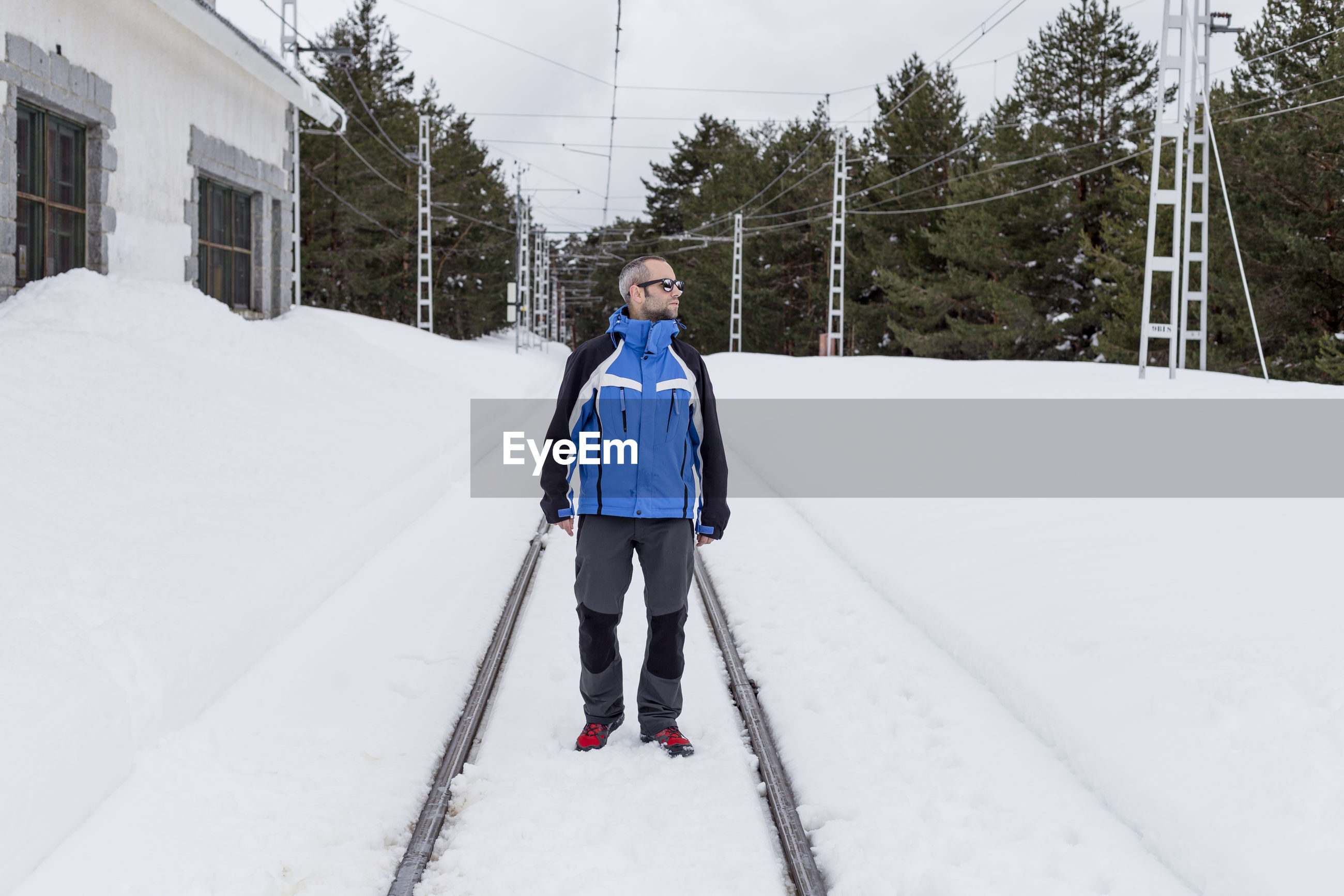 Man standing on snow covered railroad tracks during winter