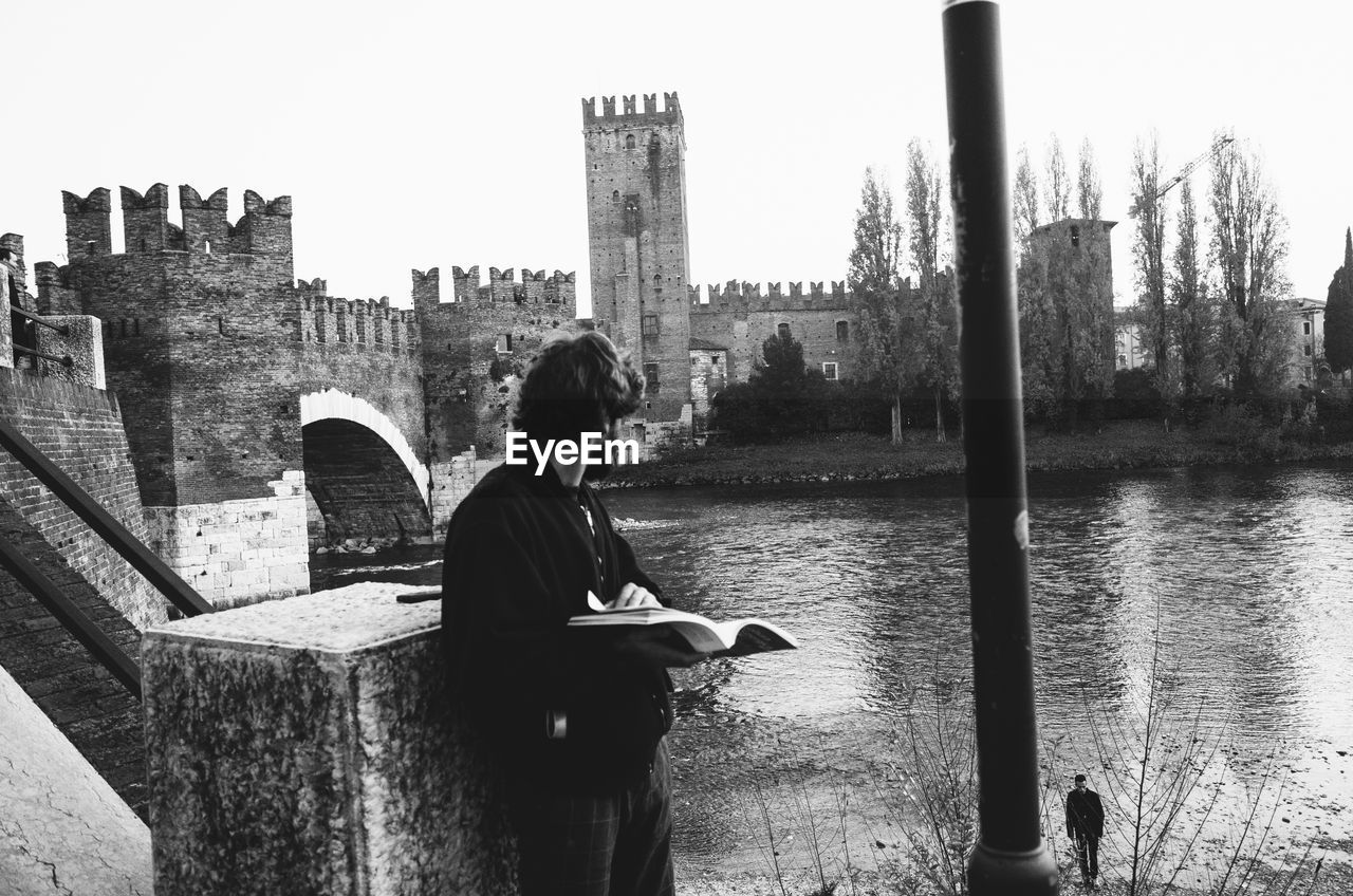 Man holding book and standing against river