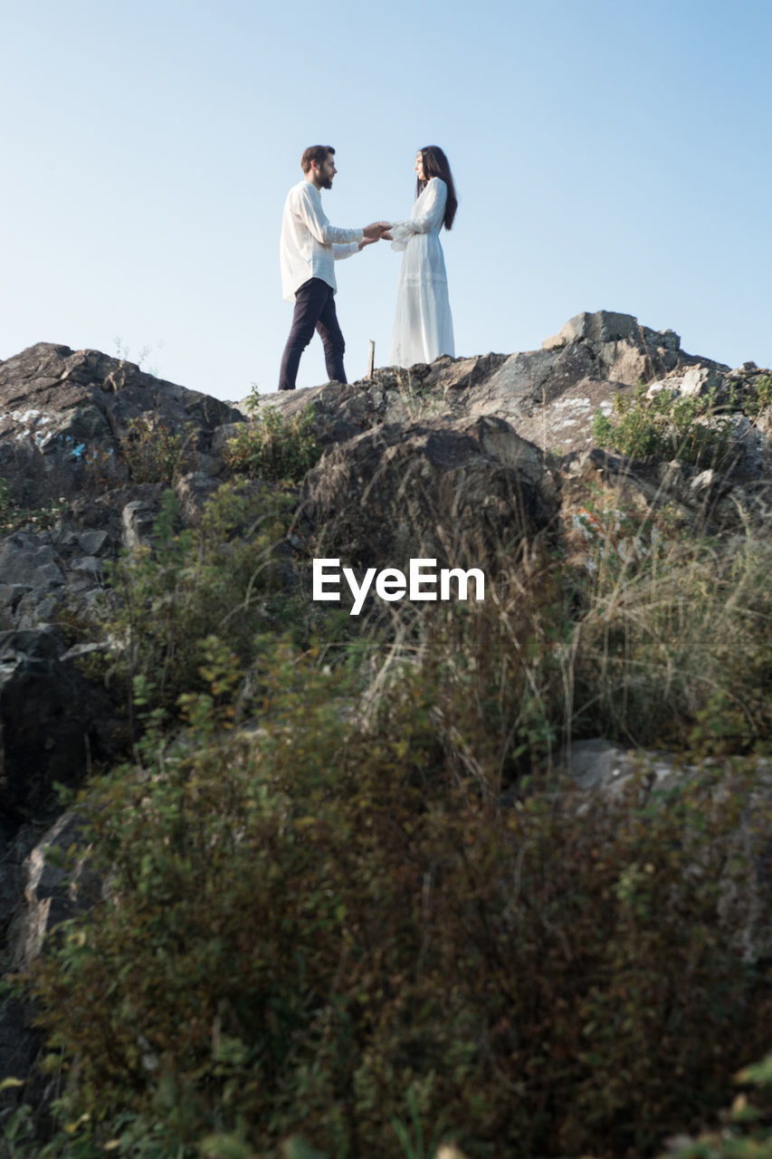 rock, sky, two people, nature, rock - object, real people, leisure activity, low angle view, full length, young adult, lifestyles, solid, women, emotion, people, day, togetherness, couple - relationship, young men, standing, outdoors, positive emotion
