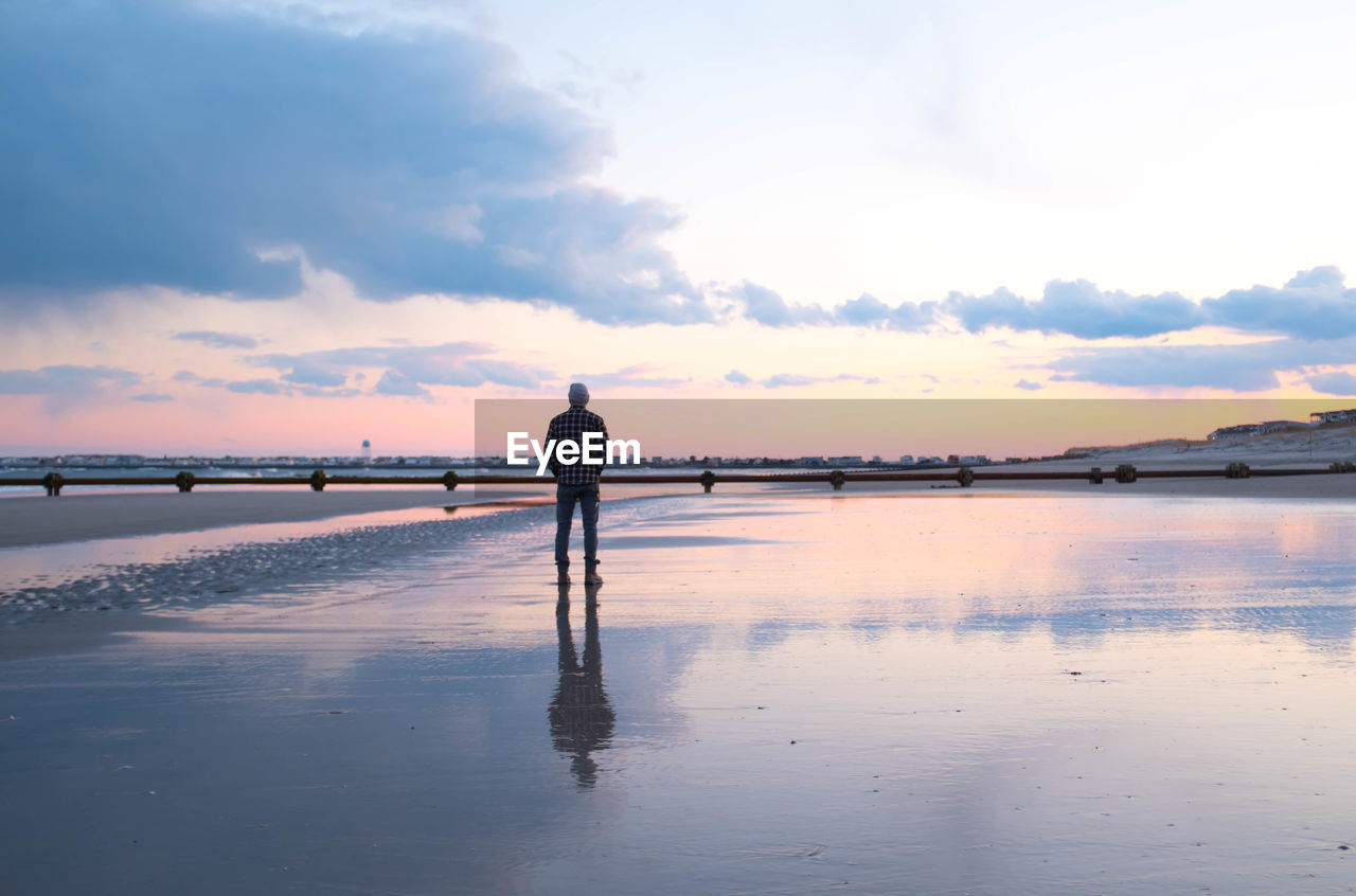 sky, cloud - sky, reflection, one person, water, beauty in nature, real people, nature, scenics - nature, sunset, full length, standing, men, lifestyles, sea, leisure activity, rear view, tranquility, land, outdoors