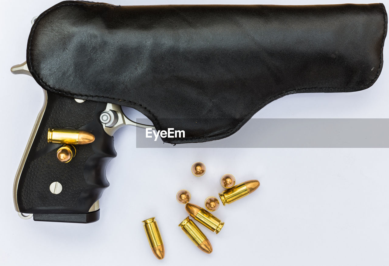 Close-up of gun and bullets over black background