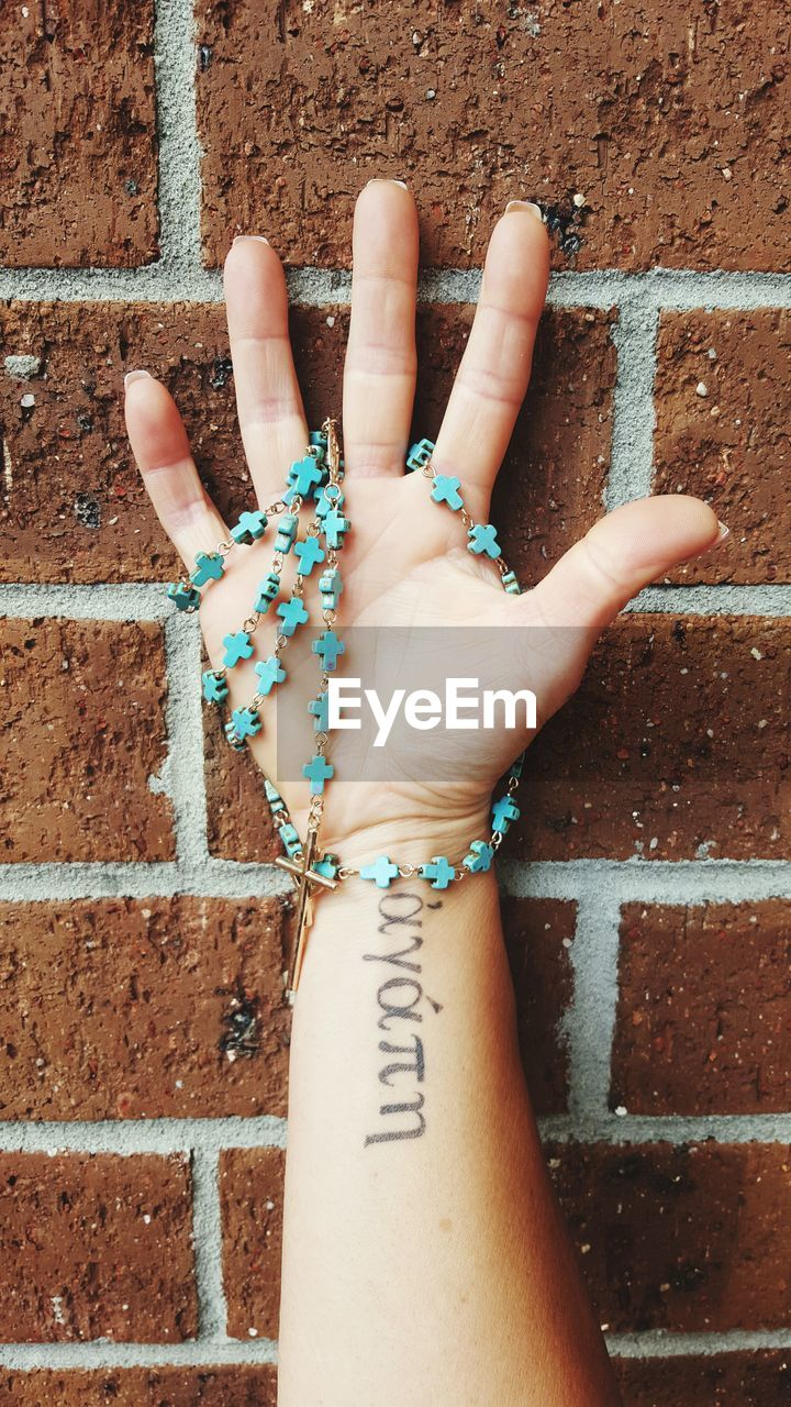 Cropped Image Of Tattooed Hand Holding Rosary Beads Against Brick Wall