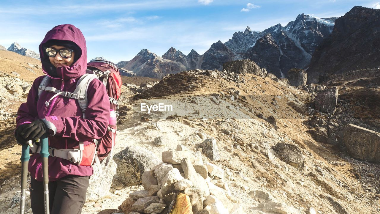 Portrait of backpacker standing on mountain