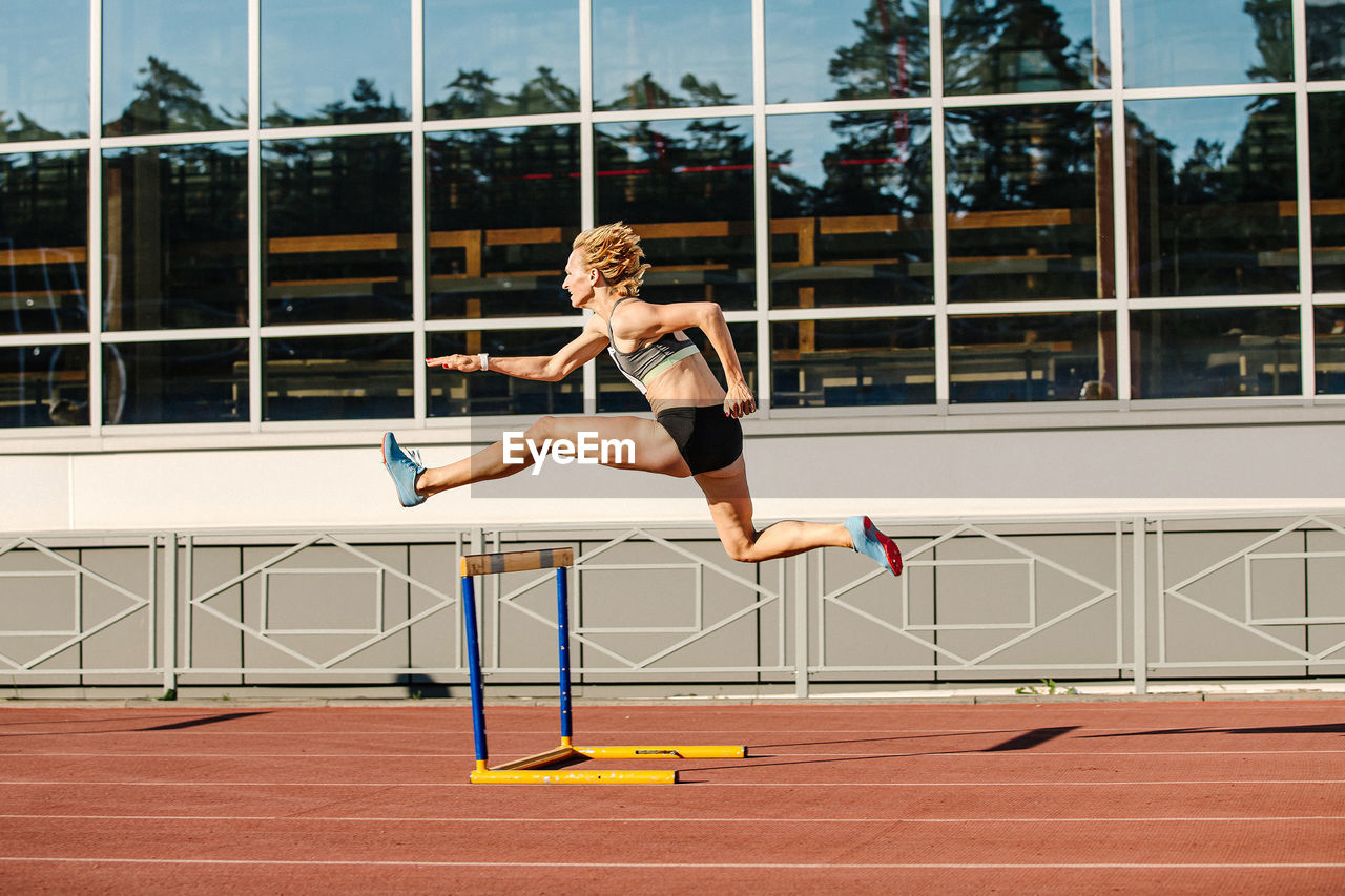 Woman athlete runnner running hurdles in summer athletics competition