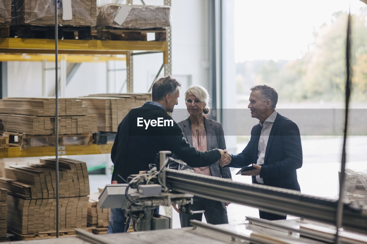Owner shaking hands with businessman standing by colleague in lumber industry
