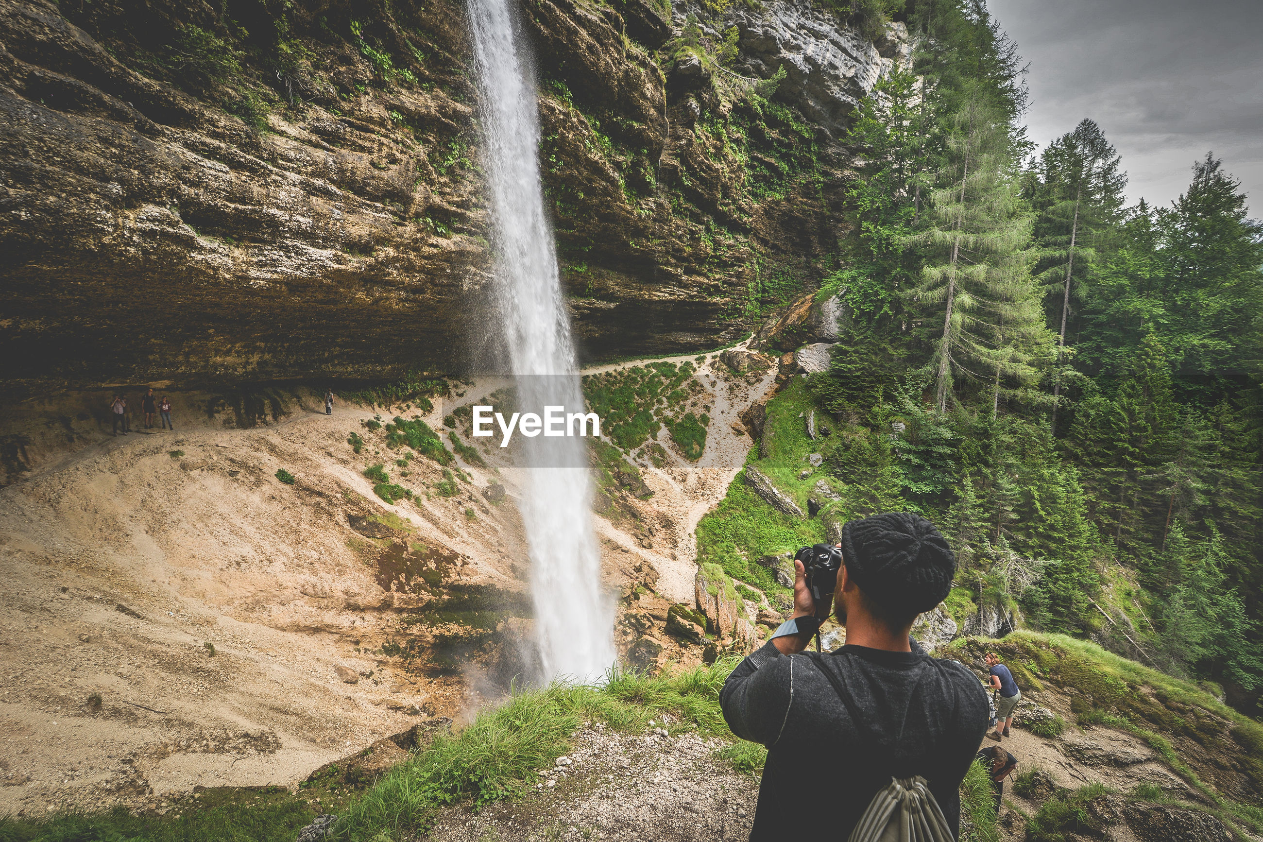 Man photographing of waterfall in forest