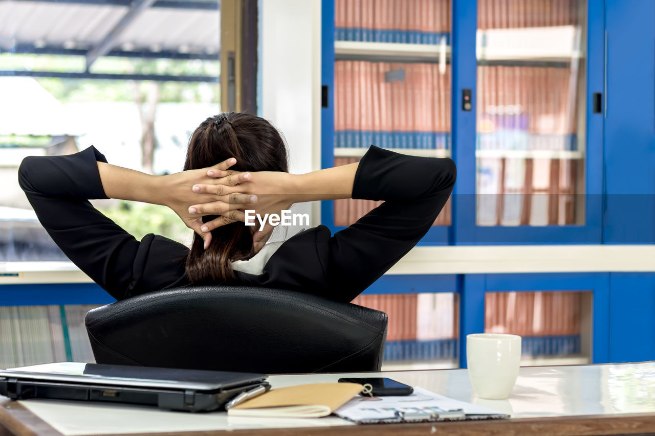 Rear view of woman with hands behind head sitting on chair in office