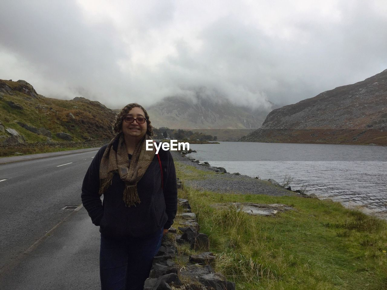 Smiling Woman Standing On Roadside By Lake Against Cloudy Sky