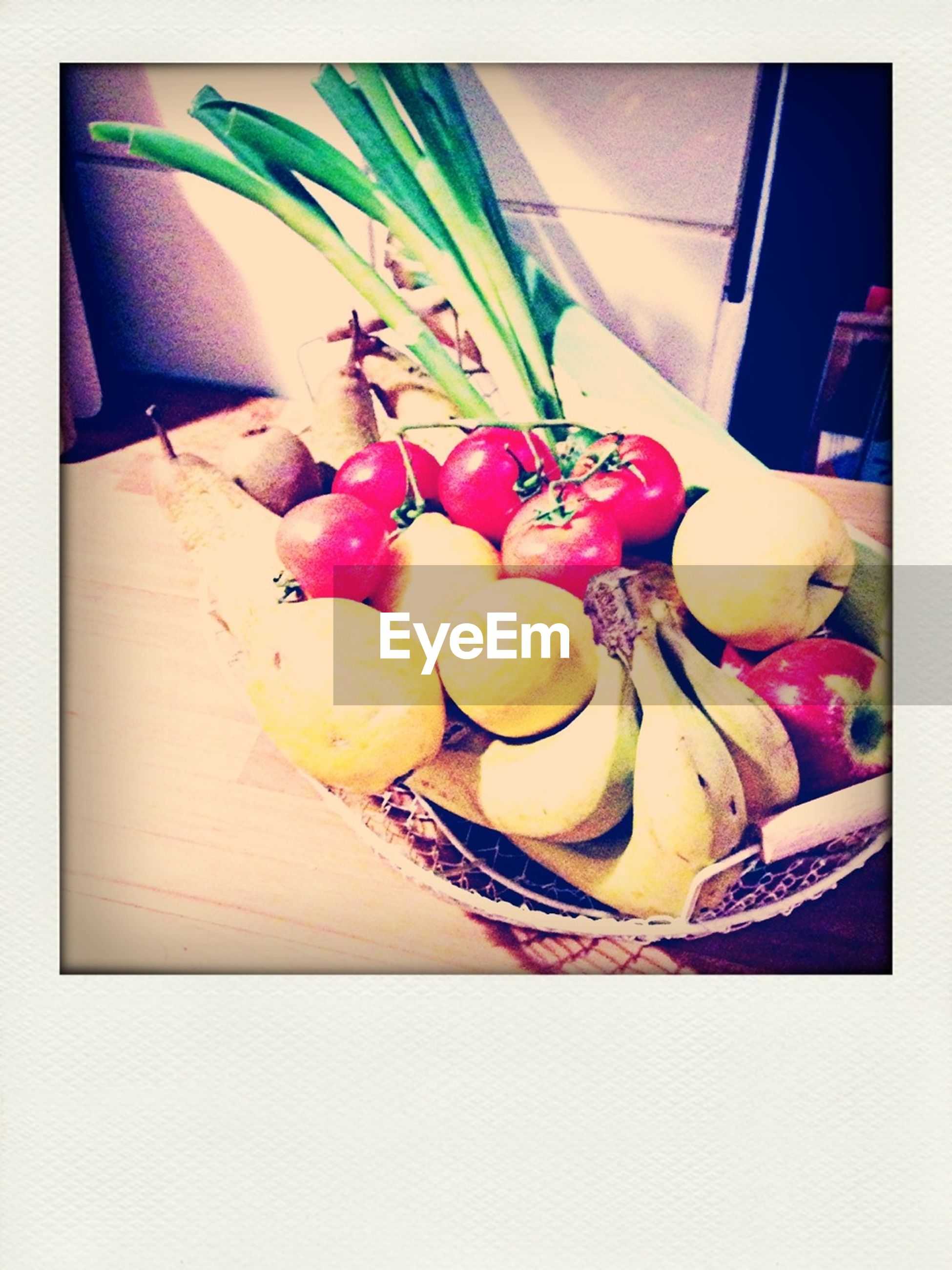Fresh fruits and vegetables in basket on table