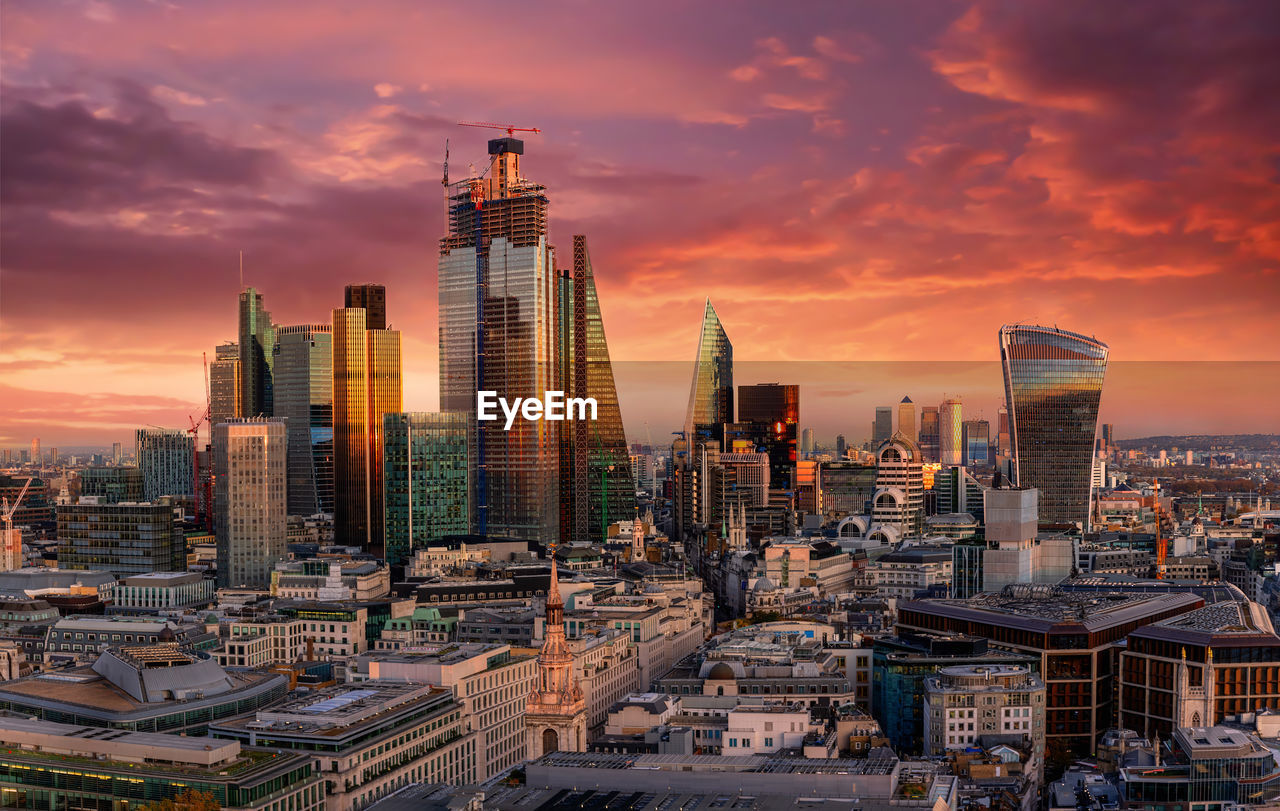 Modern Buildings In City Against Dramatic Sky During Sunset