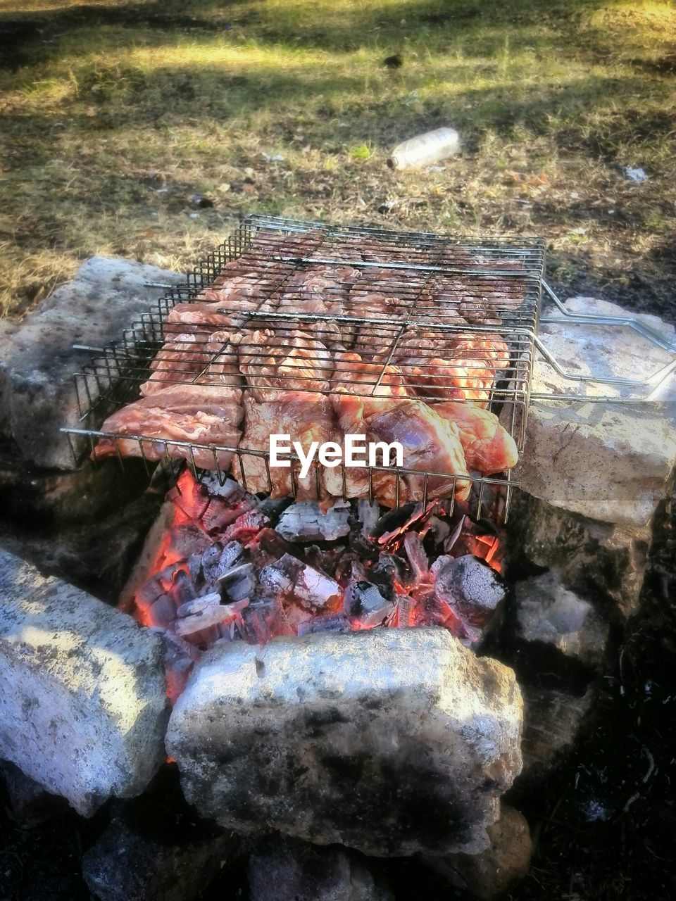 High angle view of meat in metal grate over burning coal amidst rocks in back yard