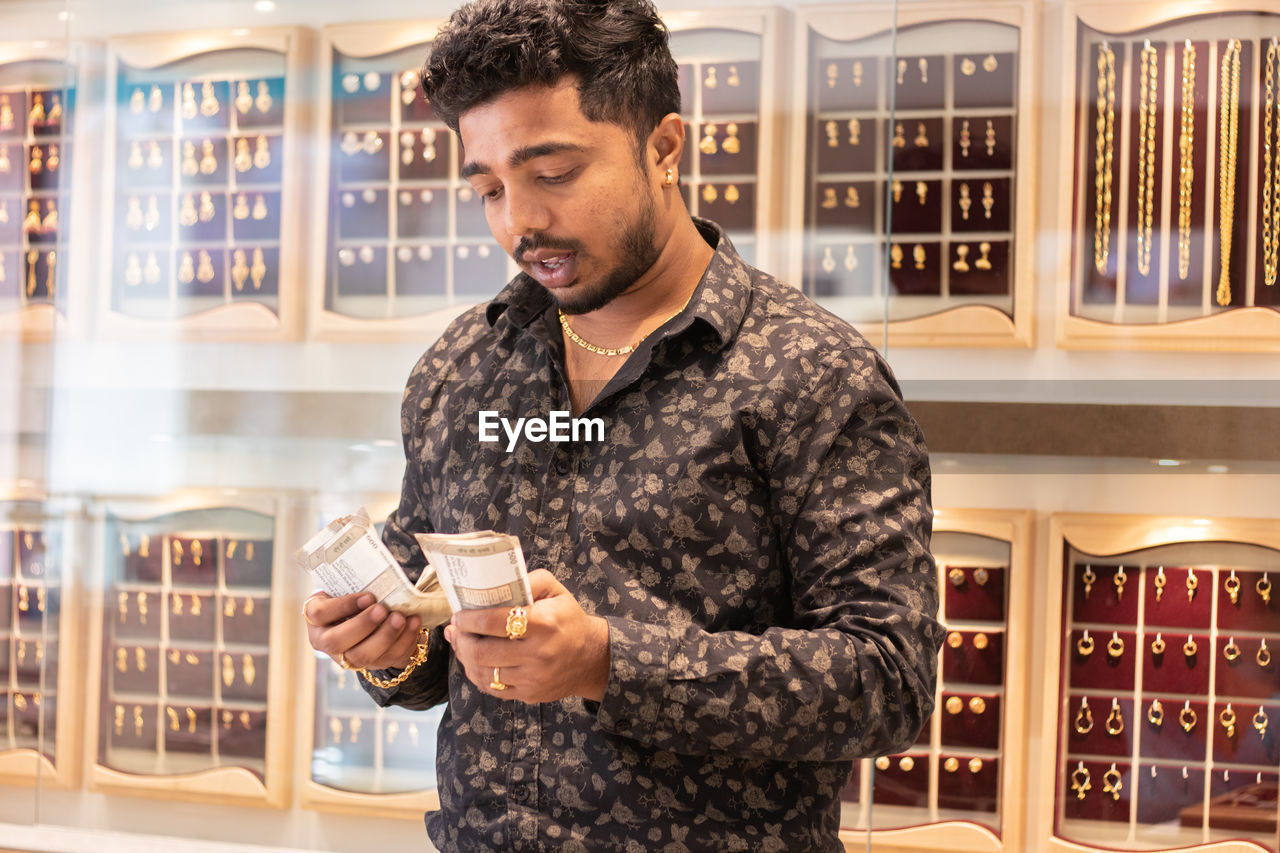 Man counting banknotes in jewelry store