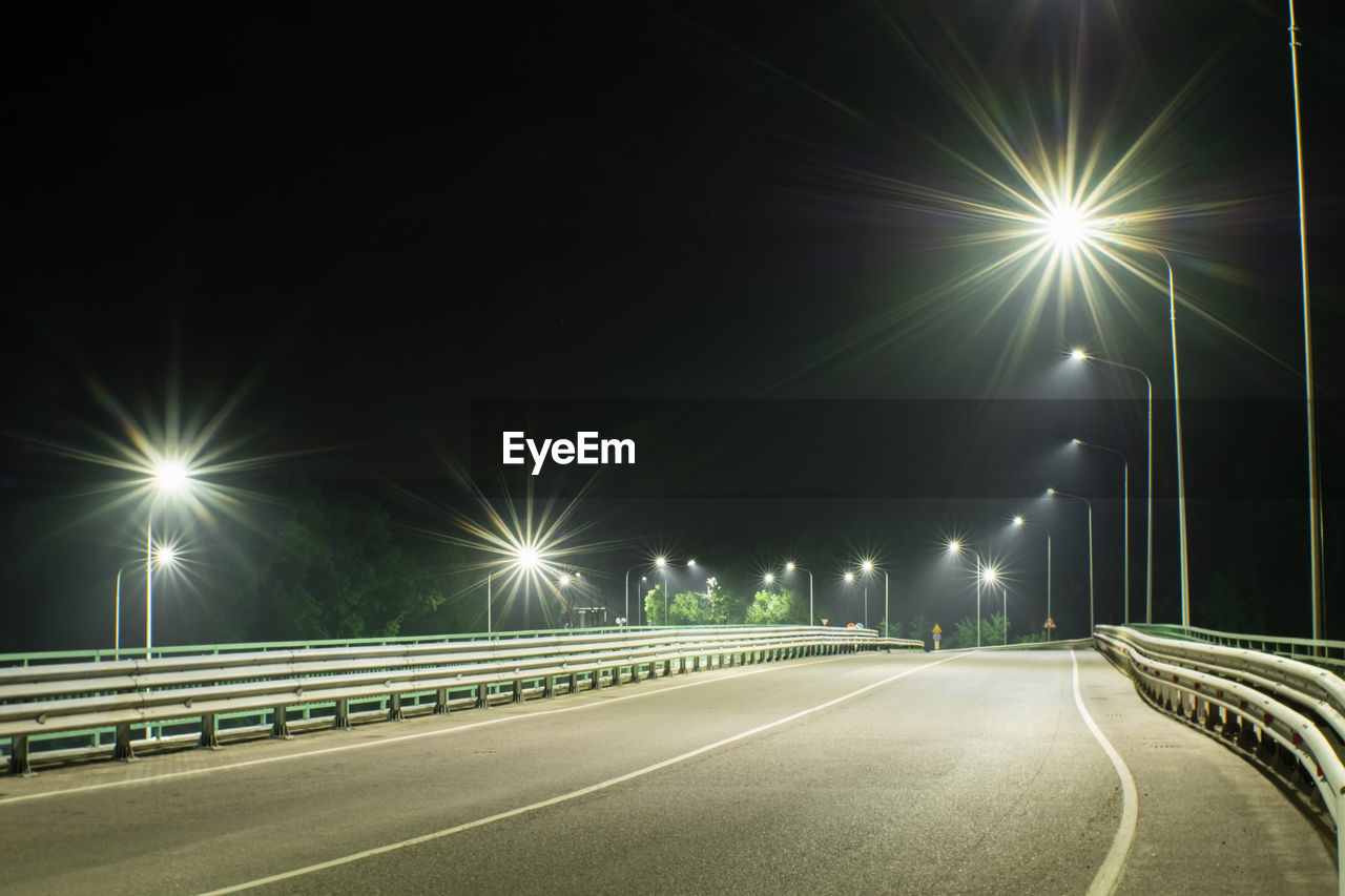 STREET LIGHT TRAILS ON ROAD AT NIGHT