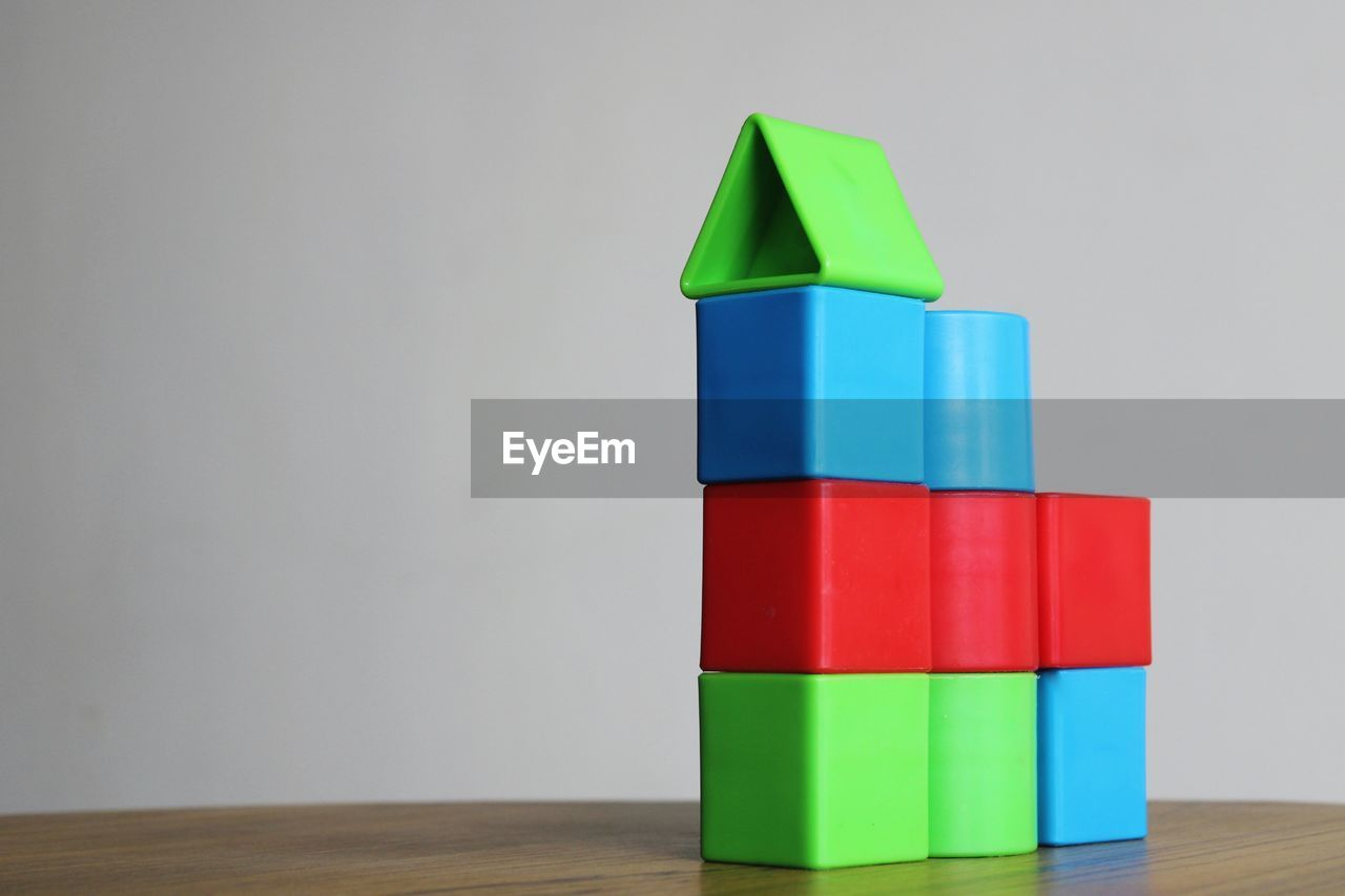 Business growth chart made of stack of multi colored toy blocks on table against white background