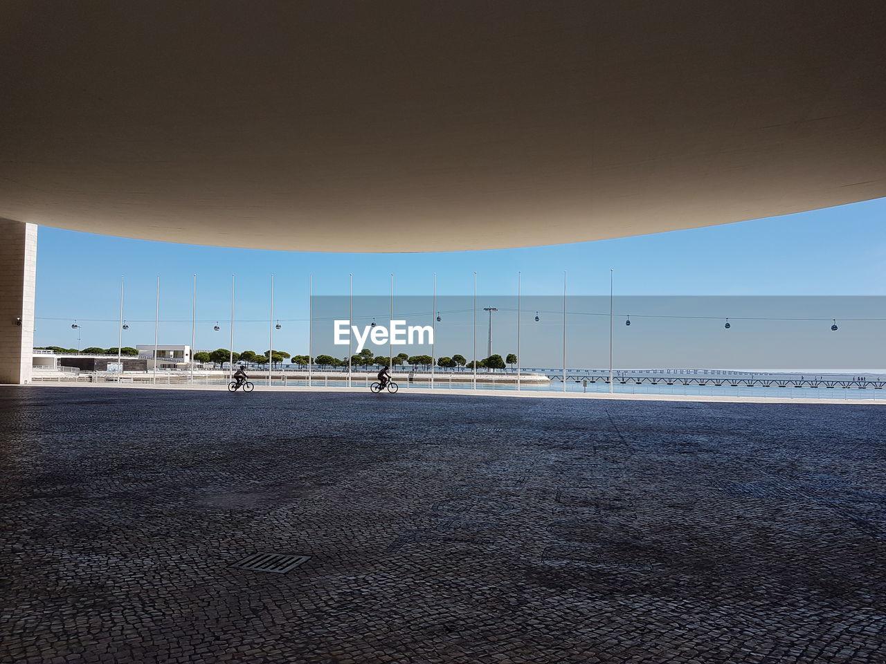 MEN ON BEACH AGAINST CLEAR SKY