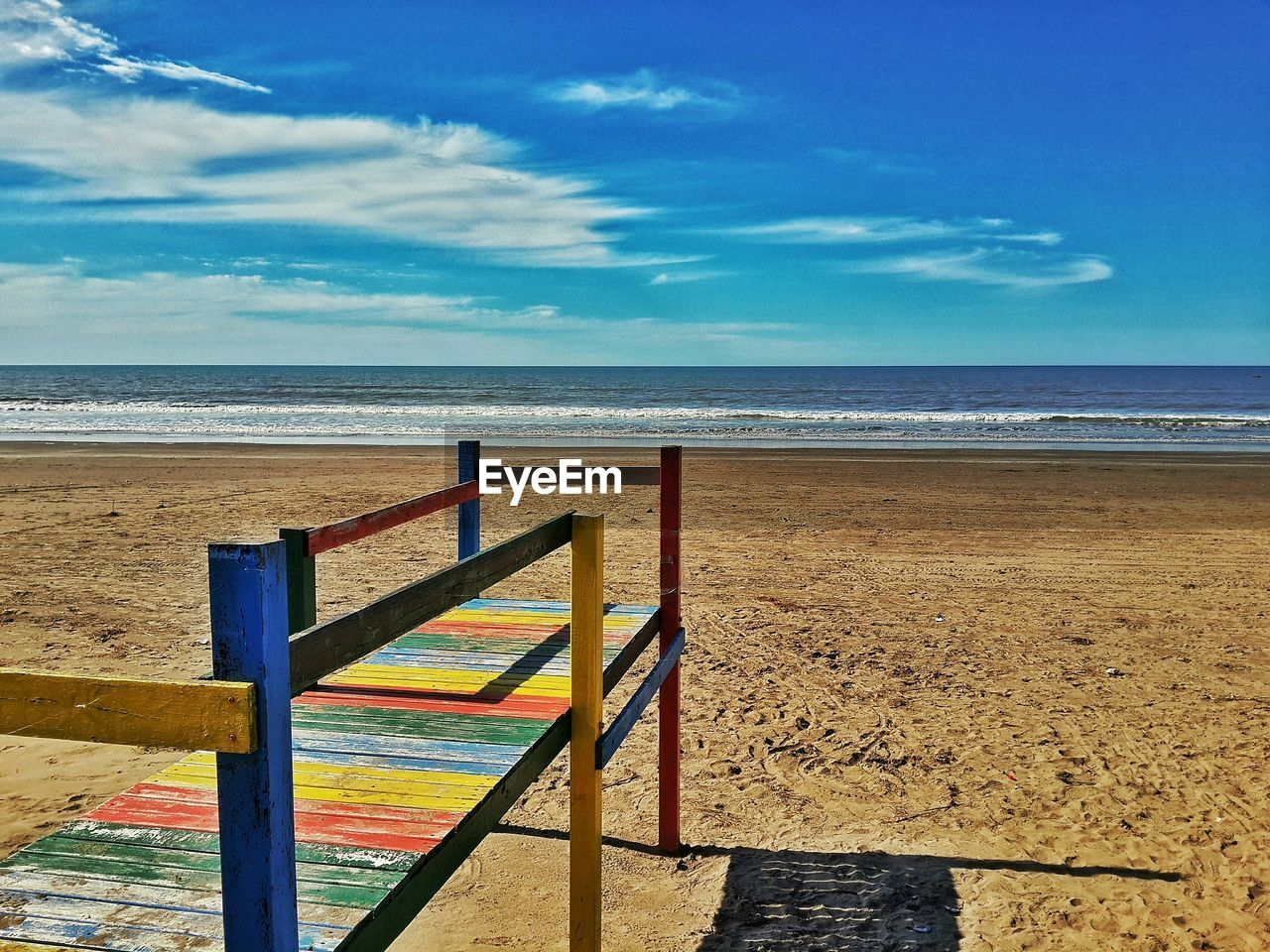 sea, horizon over water, beach, sand, sky, tranquil scene, scenics, tranquility, nature, water, beauty in nature, day, railing, sunlight, no people, outdoors, wood - material, blue, cloud - sky, vacations