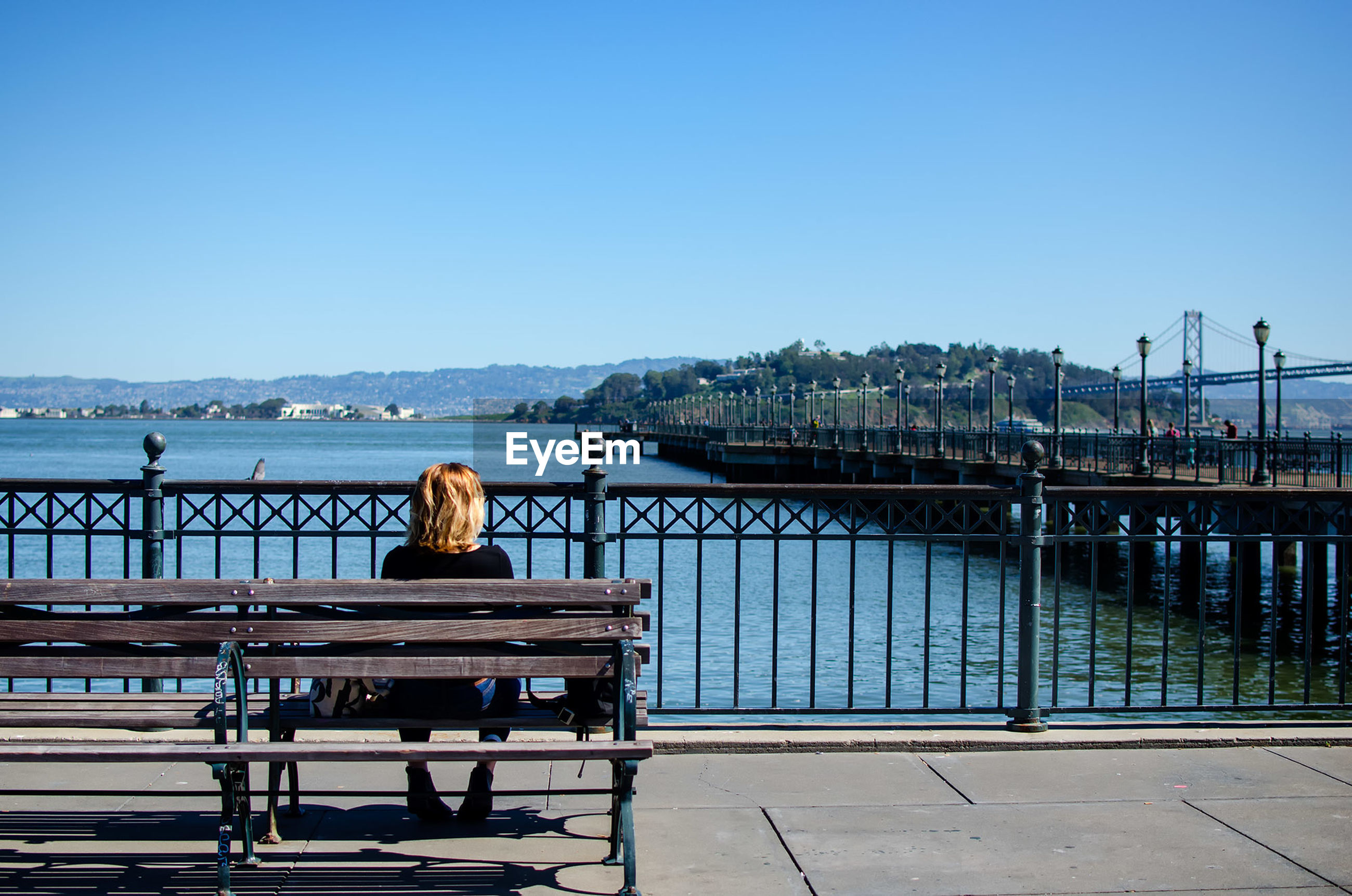 Rear view of woman sitting on bench by river against clear blue sky