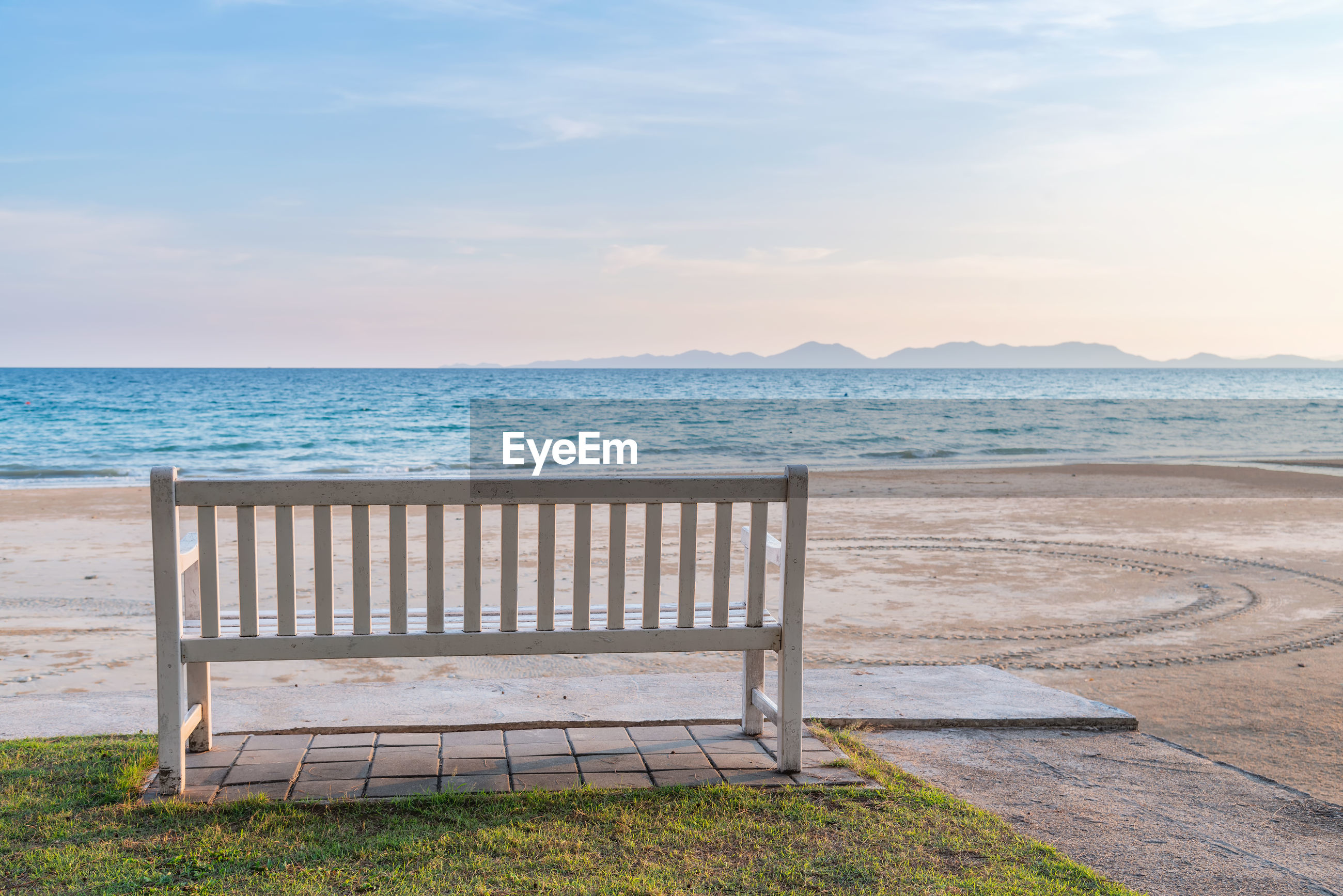Empty bench at beach against sky during sunset