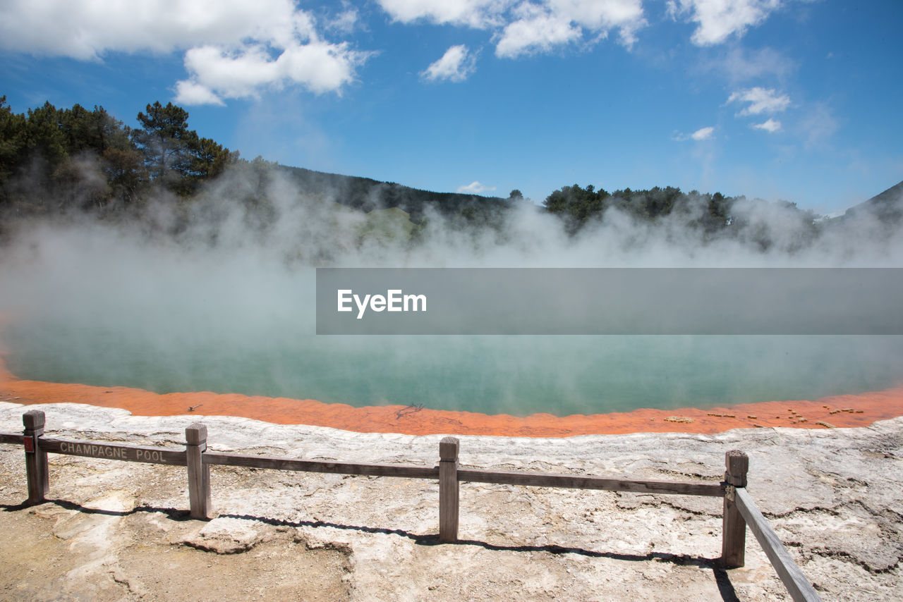 hot spring, heat - temperature, scenics - nature, beauty in nature, geology, smoke - physical structure, power in nature, physical geography, geyser, water, sky, nature, steam, tranquil scene, non-urban scene, tranquility, landscape, environment, day, railing, no people, outdoors