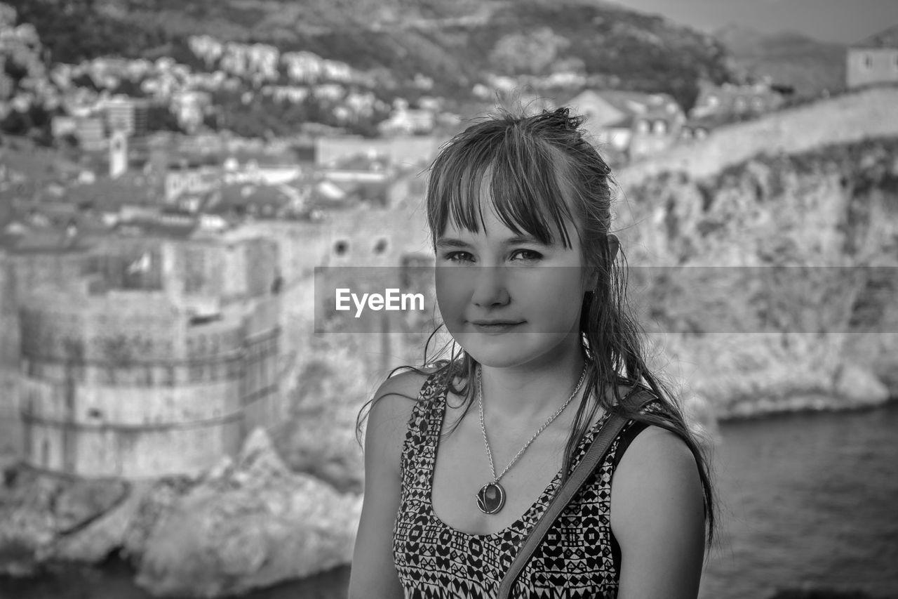 Portrait of girl standing against mountain