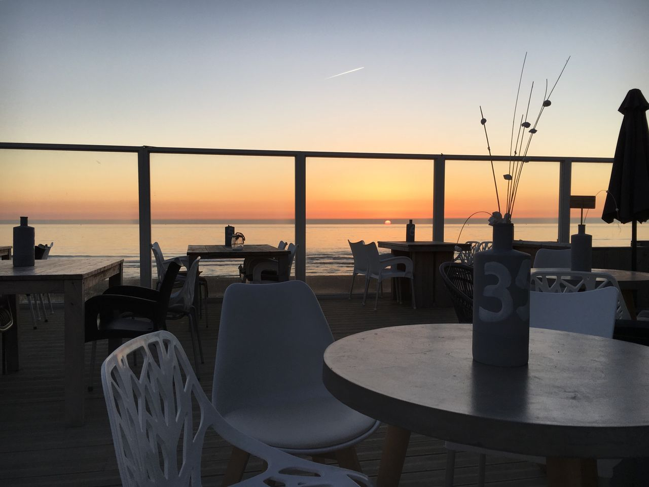 sunset, sea, chair, sky, water, horizon over water, nature, table, no people, silhouette, beauty in nature, tranquility, outdoors, scenics, sun, beach, seat, clear sky, architecture, day