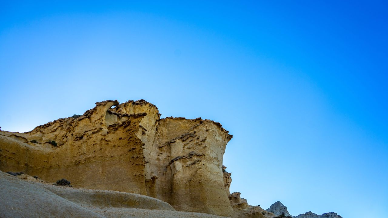sky, blue, copy space, clear sky, tranquil scene, rock formation, beauty in nature, tranquility, nature, low angle view, rock, scenics - nature, day, rock - object, non-urban scene, solid, no people, geology, environment, outdoors, formation, arid climate, eroded