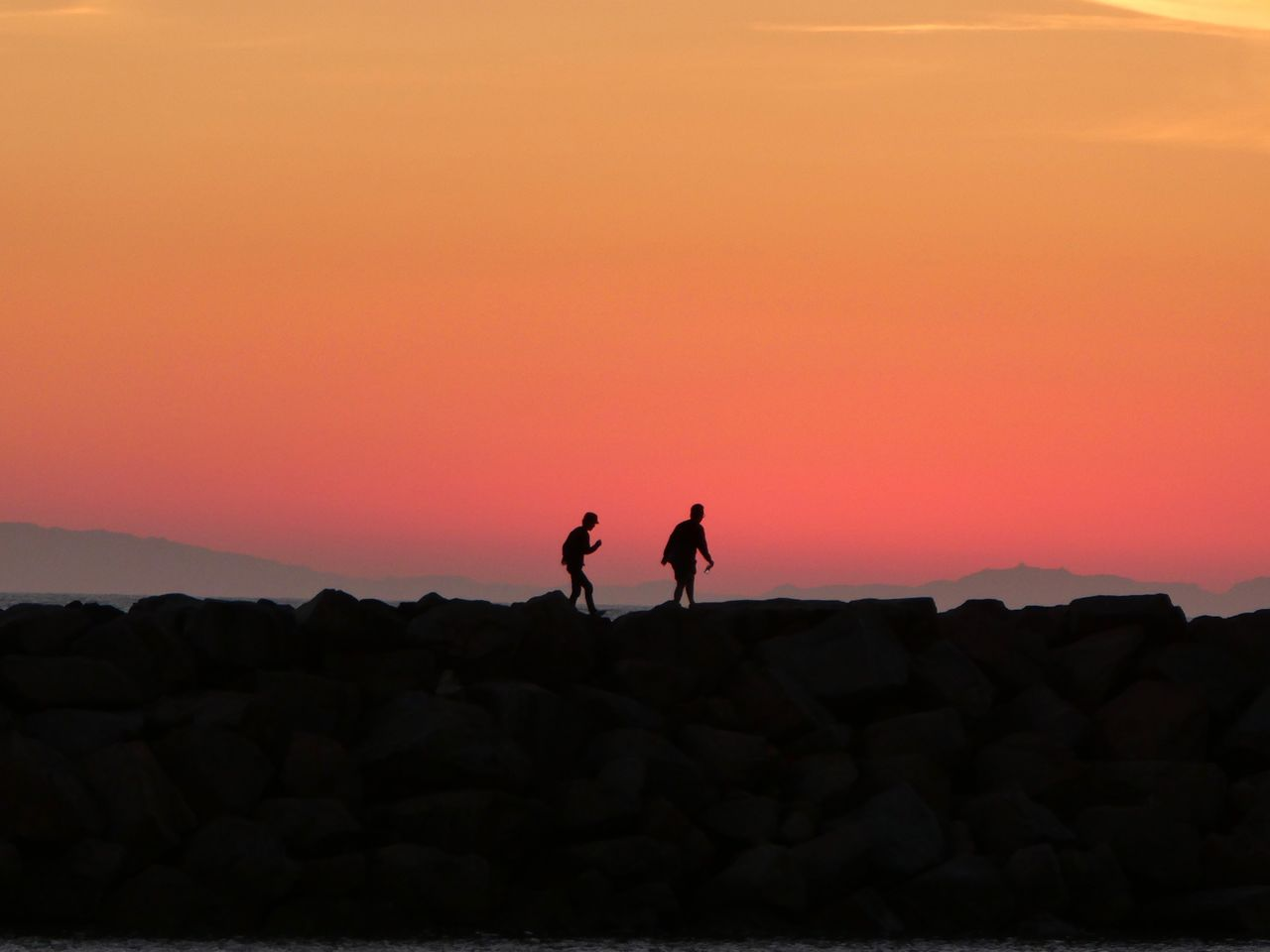 Silhouette People Standing On Rock Against Sky During Sunset
