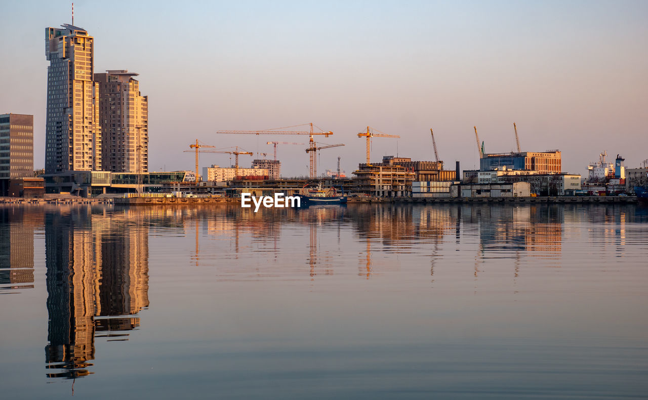 water, architecture, building exterior, reflection, sky, built structure, waterfront, no people, building, machinery, nature, crane - construction machinery, city, industry, sea, transportation, outdoors, harbor, pier, skyscraper, port