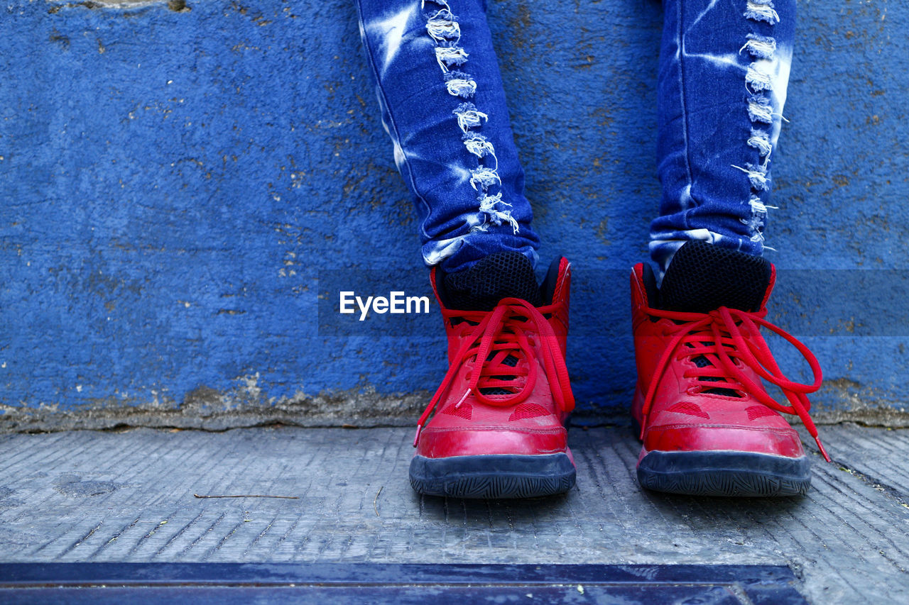 shoe, low section, one person, human body part, human leg, blue, body part, day, jeans, boot, standing, shoelace, close-up, red, pair, outdoors, unrecognizable person, casual clothing, leather, lace - fastener, human limb, human foot