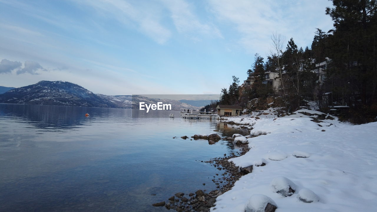 water, winter, cold temperature, sky, snow, beauty in nature, scenics - nature, tranquility, tranquil scene, nature, mountain, cloud - sky, no people, day, lake, waterfront, tree, non-urban scene, outdoors, snowcapped mountain