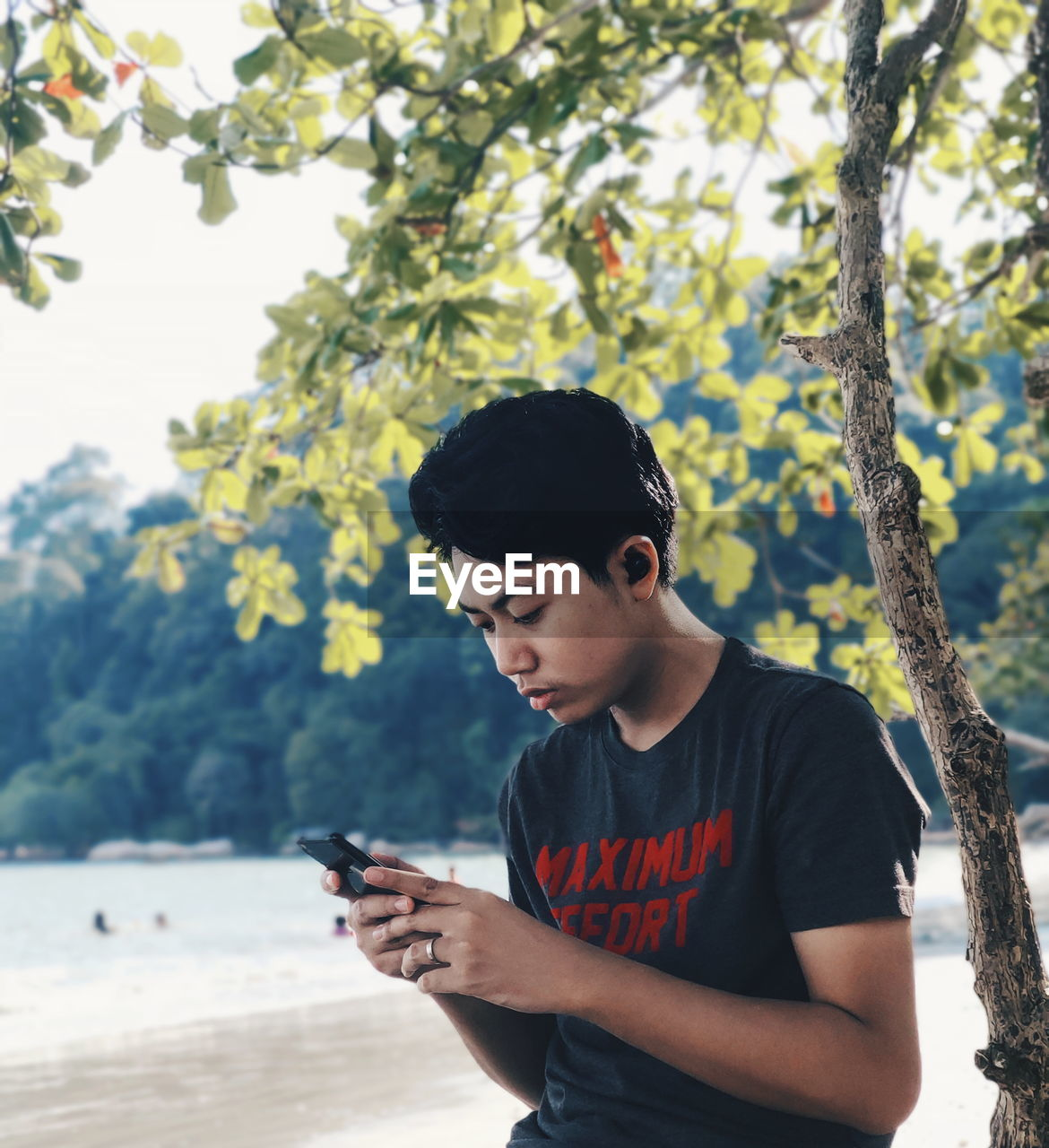 Young man using phone while standing outdoors