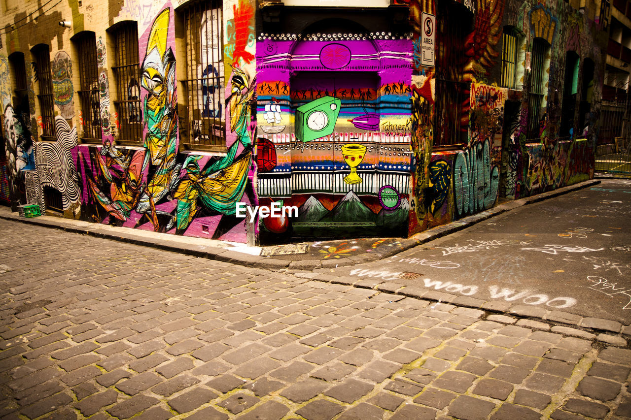 multi colored, footpath, art and craft, creativity, street, architecture, built structure, no people, city, graffiti, building exterior, cobblestone, day, outdoors, sidewalk, pattern, variation, craft, paving stone, building