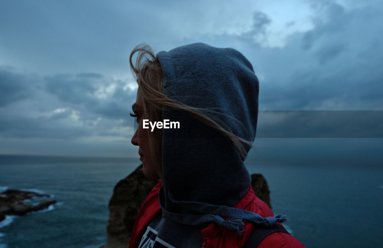Side view of thoughtful woman looking at sea against cloudy sky