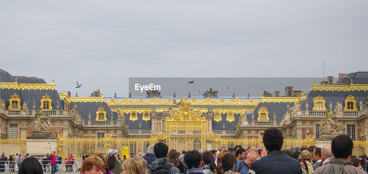 People Visiting Palace Of Versailles Against Sky