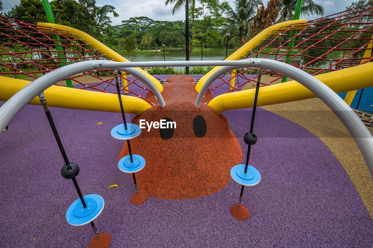 playground, childhood, outdoor play equipment, park, park - man made space, day, multi colored, metal, nature, outdoors, hanging, plant, absence, circle, shape, fun, yellow, jungle gym, merry-go-round