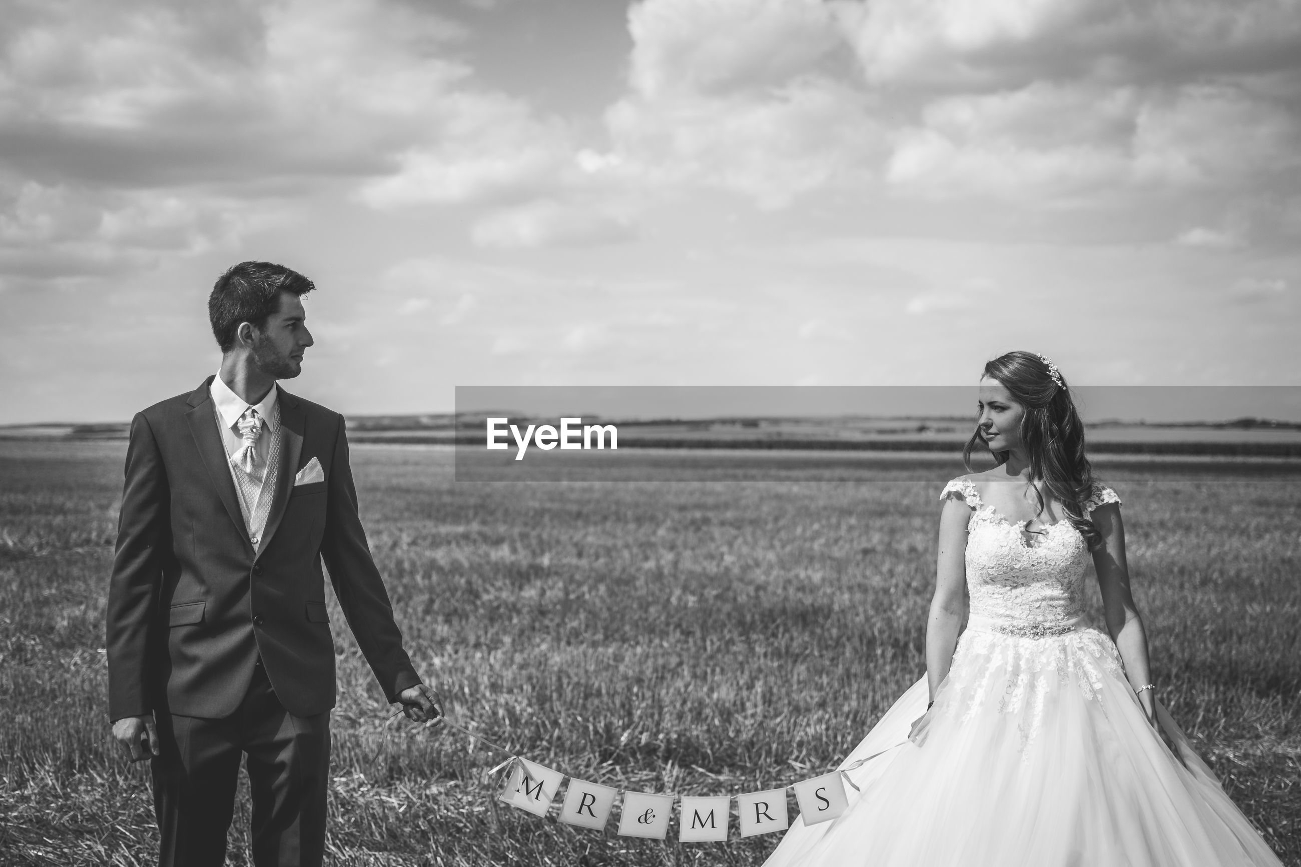 Couple standing together on a field on wedding day.