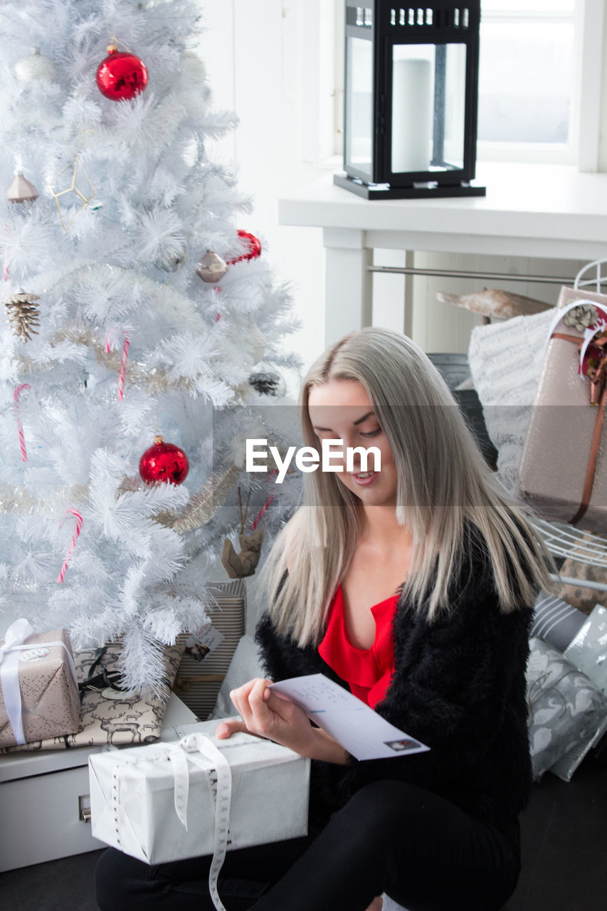 one person, christmas, young adult, smiling, young women, indoors, real people, lifestyles, women, celebration, christmas tree, blond hair, happiness, tree, sitting, hair, front view, emotion, hairstyle, christmas ornament, beautiful woman