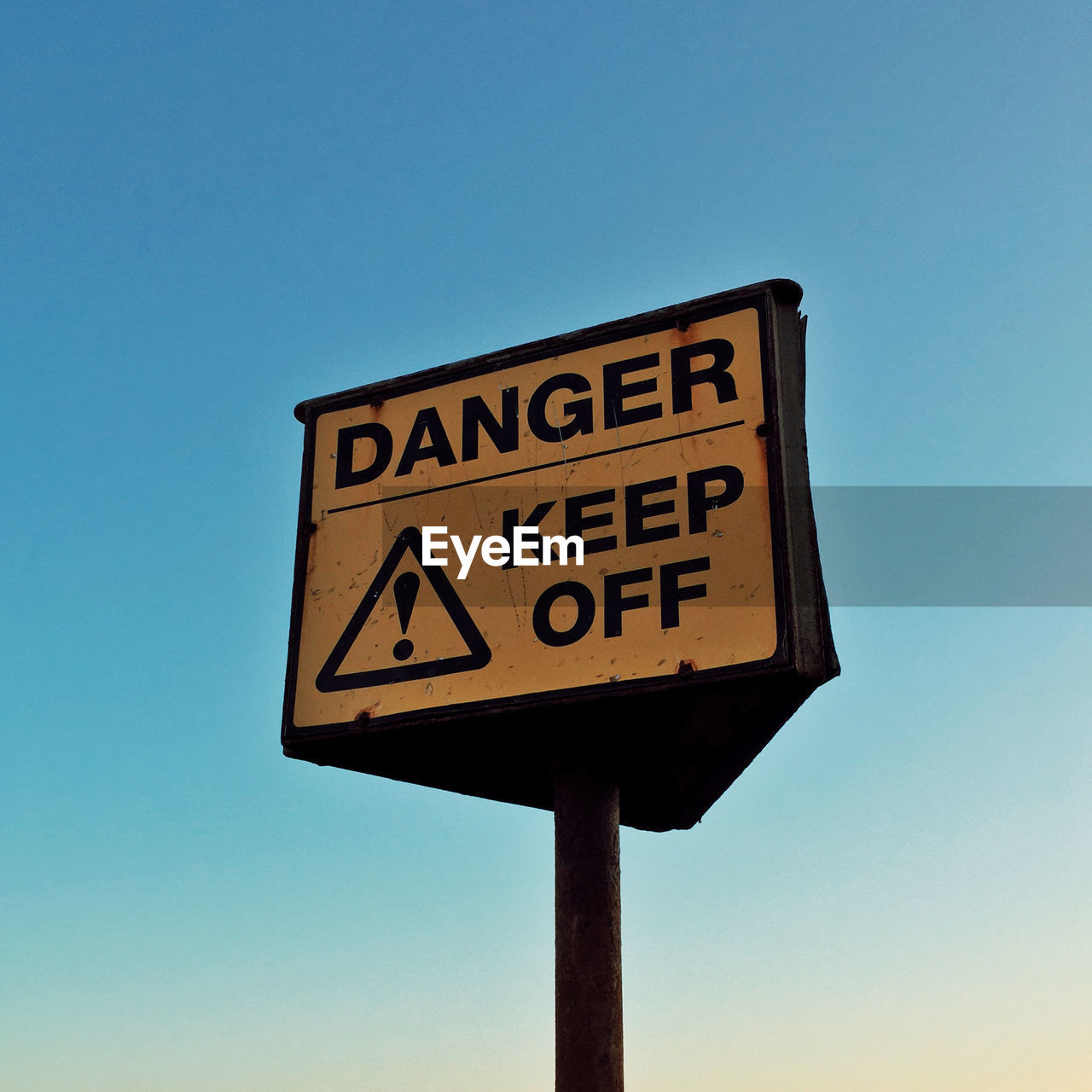 Low angle view of warning sign against blue sky