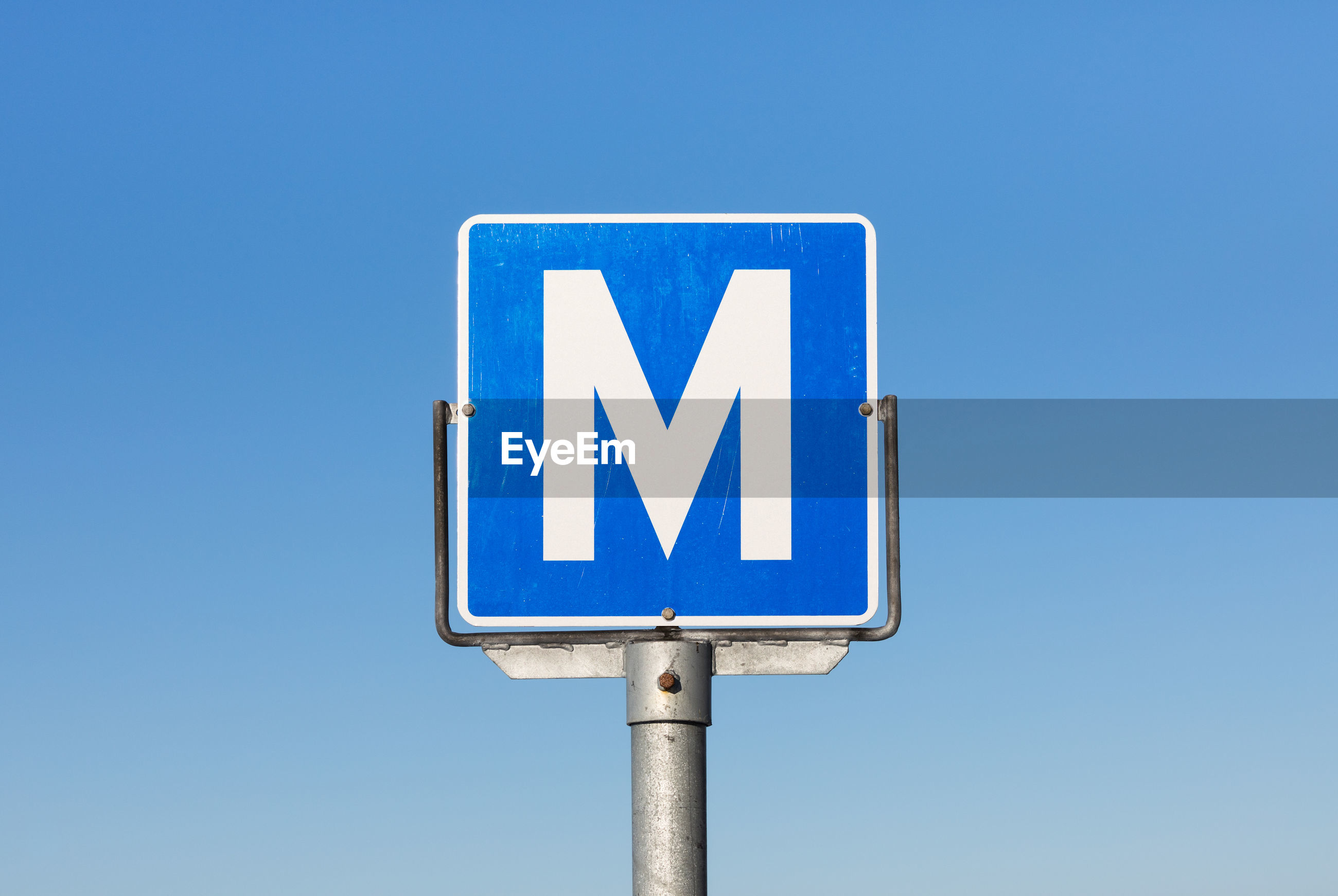 Low angle view of m sign against clear blue sky