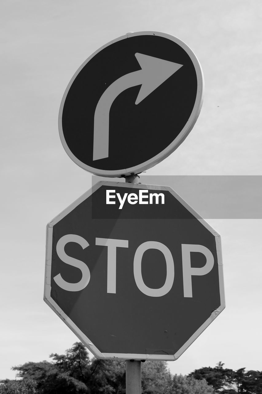 communication, road sign, guidance, circle, text, day, warning sign, outdoors, no people, speed limit sign, close-up, low angle view, sky, information medium