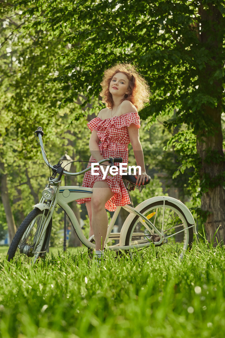 WOMAN WITH BICYCLE ON FIELD
