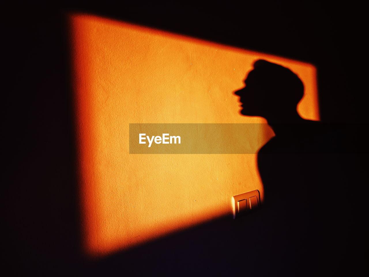 Shadow of man on wall at night